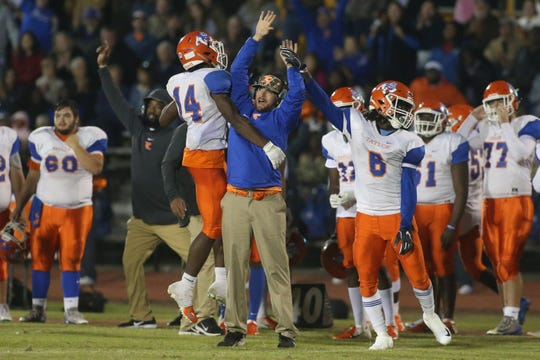 Taylor County's Robert Glanton (14) and  Zoe Roberts (6) celebrate a Bulldogs touchdown with one of their coaches during a Region 1-3A final at Florida High on Friday, Nov. 23, 2018.