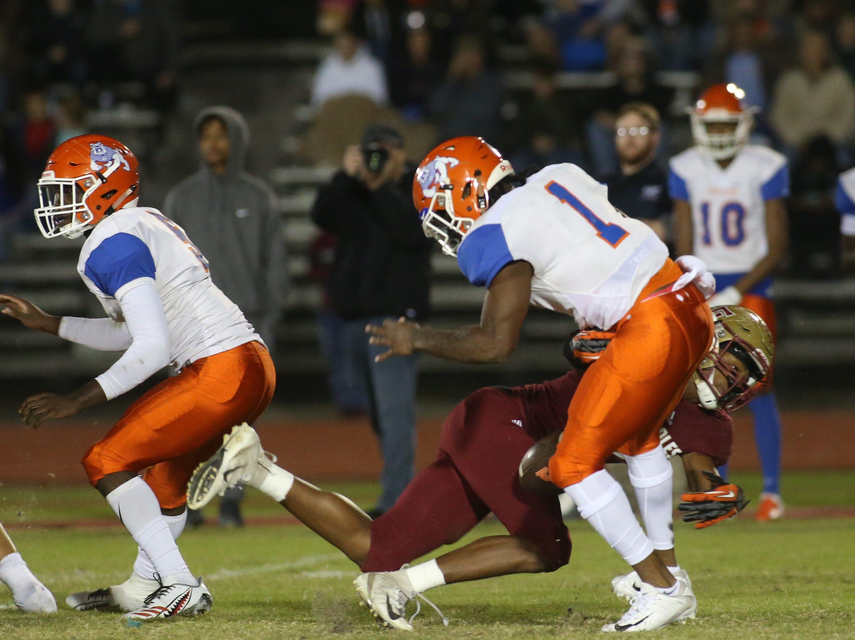 Taylor County Bulldog quarterback Da'corian Bellamy (1) gets sacked by the defense as the Taylor County Bulldogs play the Florida High Seminoles in a Region 1-3A final on Friday, Nov. 23, 2018.