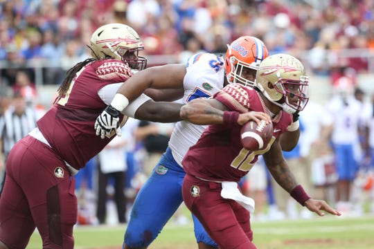 Florida State Seminoles quarterback Deondre Francois (12) dodges the defense while looking to pass as the Florida State Seminoles take on their rival the Florida Gators in college football at Doak S. Campbell Stadium, Saturday, Nov. 24, 2018.