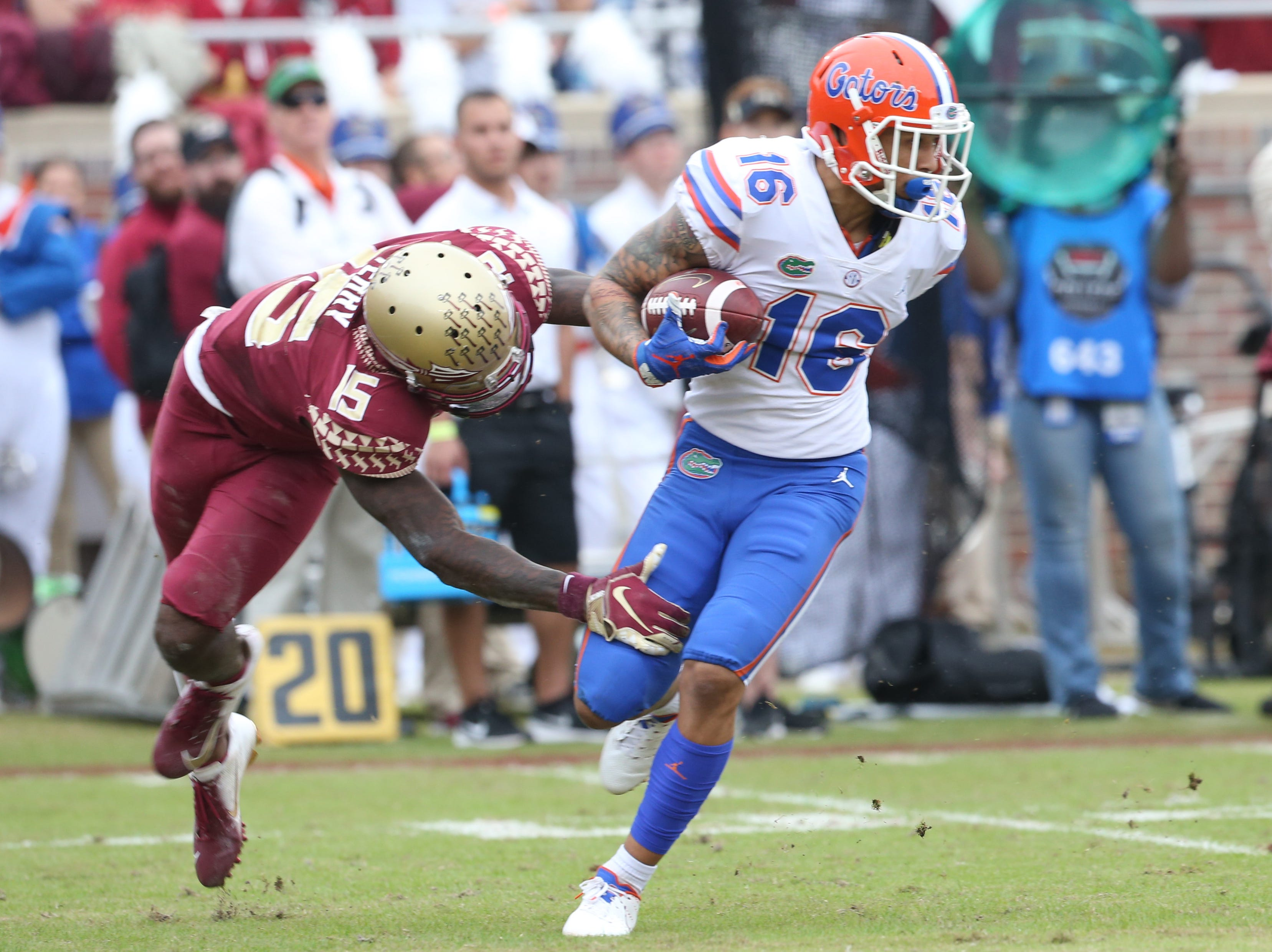 Florida Gators wide receiver Freddie Swain (16) fights off a tackle from Florida State Seminoles defensive back Carlos Becker III (15) as the Florida State Seminoles take on their rival the Florida Gators in college football at Doak S. Campbell Stadium, Saturday, Nov. 24, 2018.