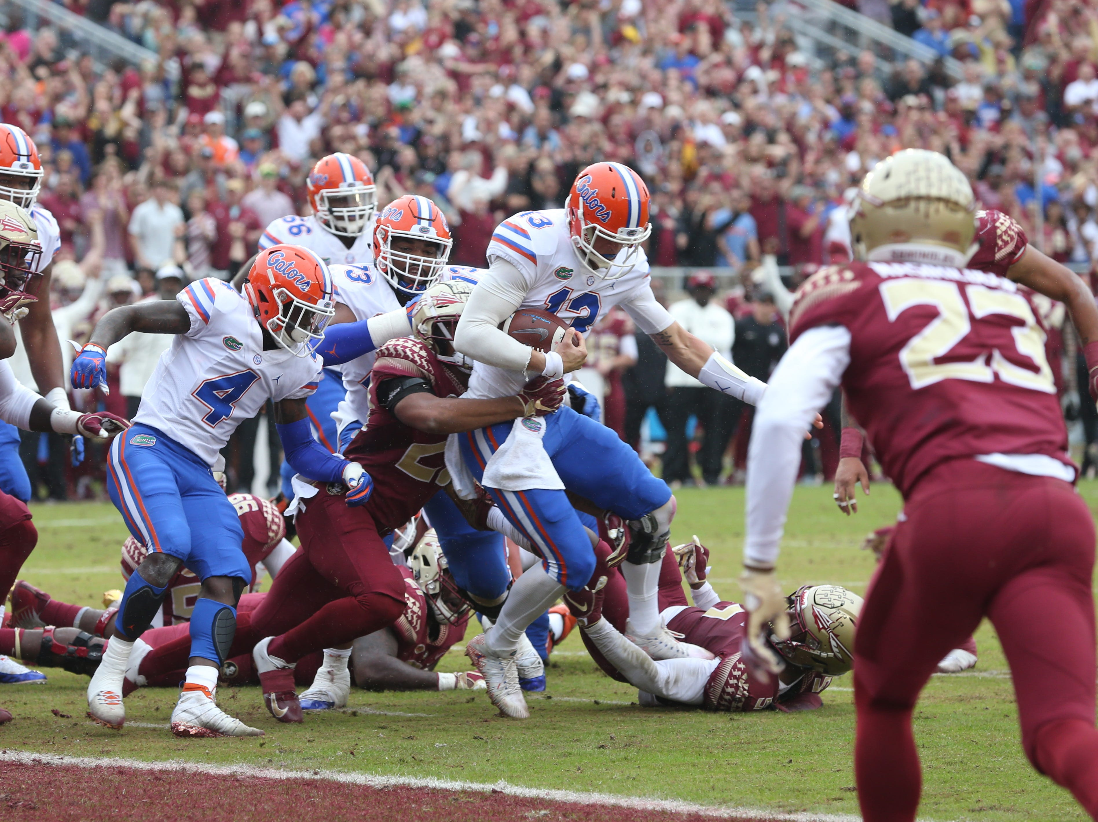 Florida Gators quarterback Feleipe Franks (13) fights off tackles as he tries to run for a touchdown as the Florida State Seminoles take on their rival the Florida Gators in college football at Doak S. Campbell Stadium, Saturday, Nov. 24, 2018.