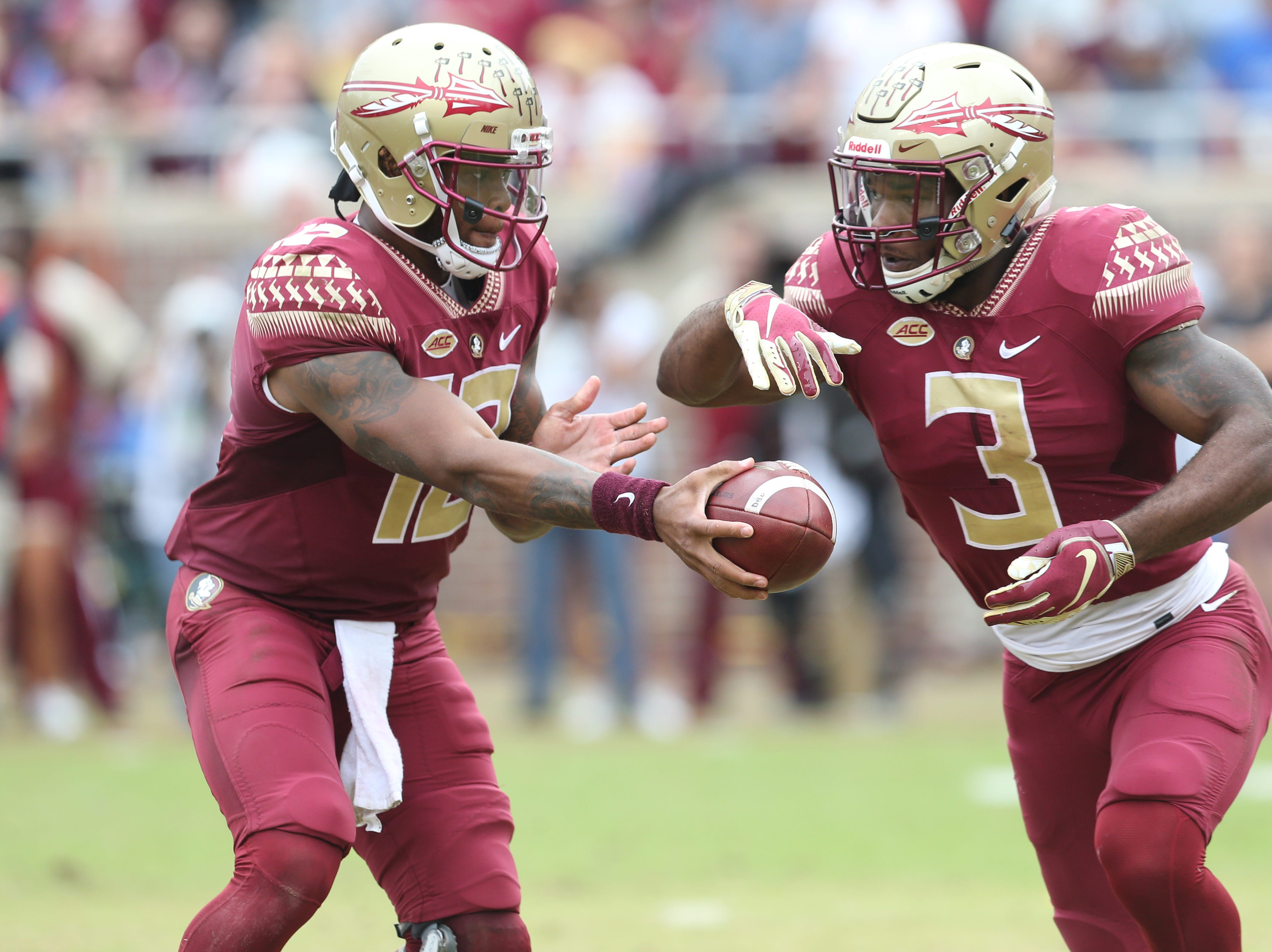 Florida State Seminoles quarterback Deondre Francois (12) hands off the ball to Florida State Seminoles running back Cam Akers (3) as the Florida State Seminoles take on their rival the Florida Gators in college football at Doak S. Campbell Stadium, Saturday, Nov. 24, 2018.