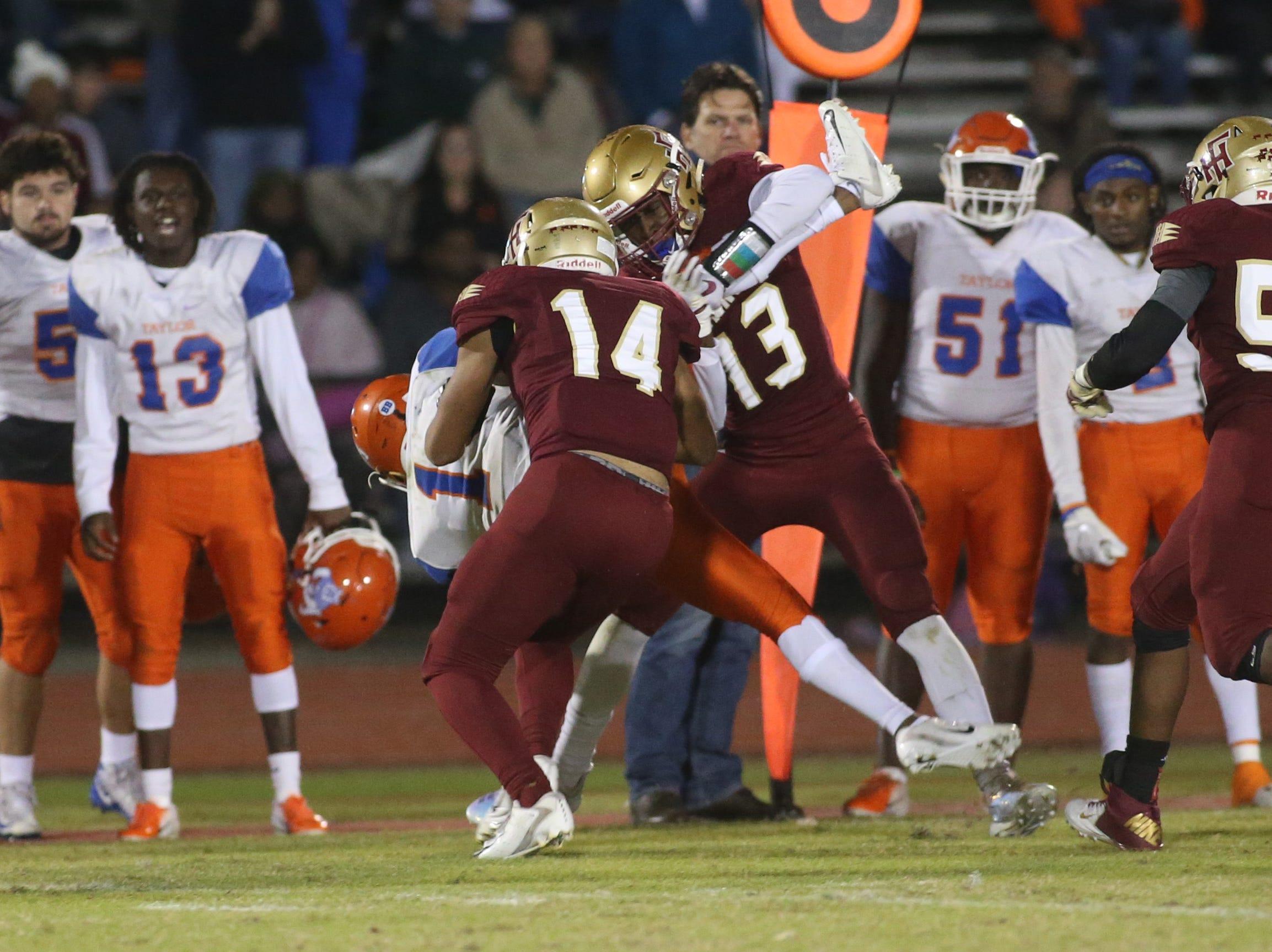Florida High Seminoles free safety Raymond Woodle (13) and middle linebacker Jordan Gilley (14) tackle Taylor County Bulldog quarterback Da'corian Bellamy (1) as the Taylor County Bulldogs play the Florida High Seminoles in a Region 1-3A final on Friday, Nov. 23, 2018.
