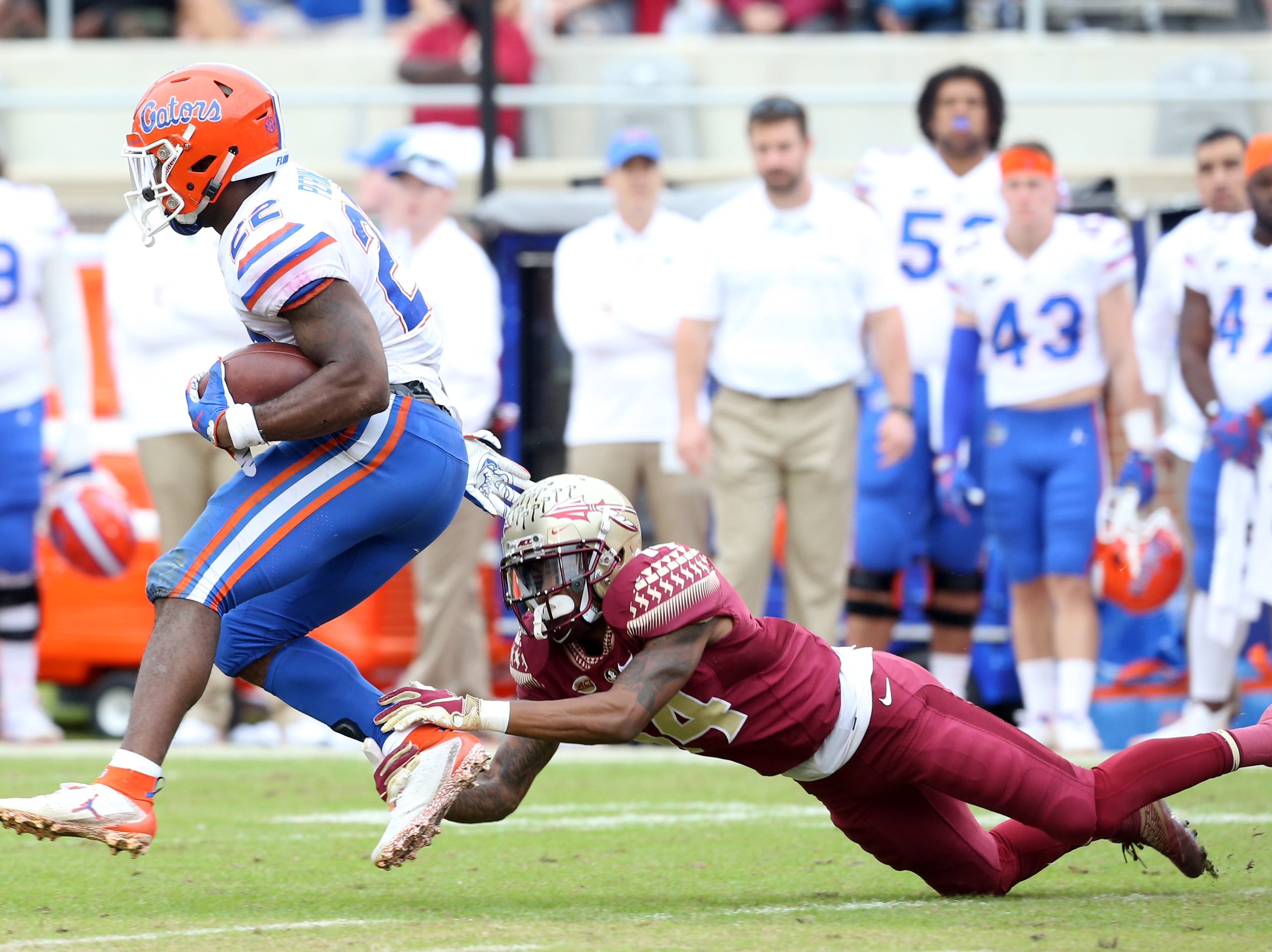Florida Gators running back Lamical Perine (22) tries to fight off a defender as the Florida State Seminoles take on their rival the Florida Gators in college football at Doak S. Campbell Stadium, Saturday, Nov. 24, 2018.