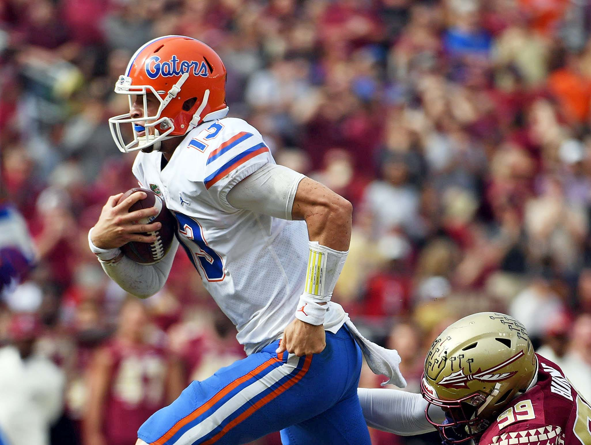 Nov 24, 2018; Tallahassee, FL, USA; Florida Gators quarterback Feleipe Franks (13) runs the ball and is tackled by Florida State Seminoles defensive end Brian Burns (99) during the first half at Doak Campbell Stadium. Mandatory Credit: Melina Myers-USA TODAY Sports