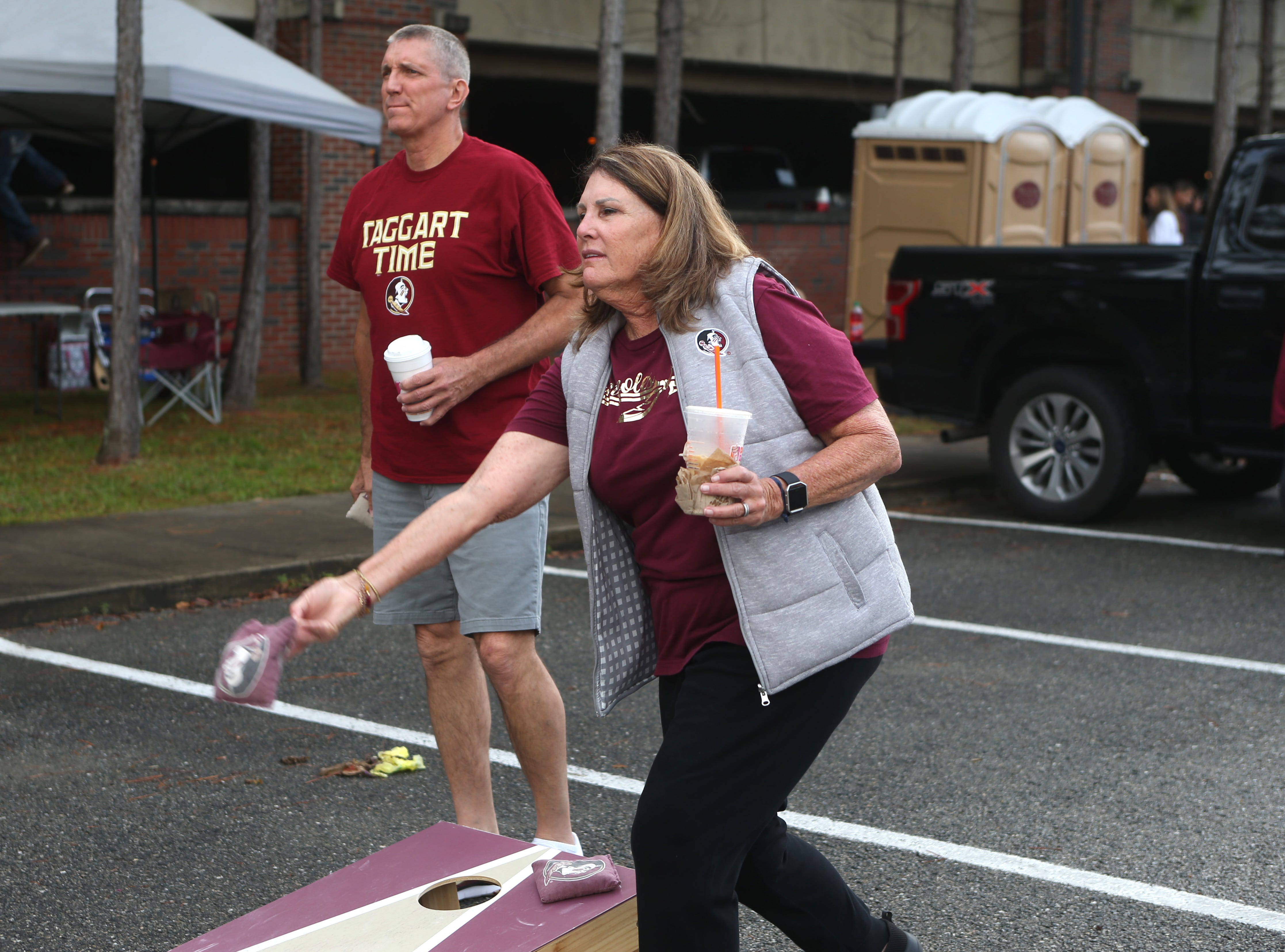 Donna Nitz plays corn hole with friends as fans tailgate before the big rivalry game between the Florida State Seminoles and the Florida Gators, Saturday, Nov. 24, 2018.