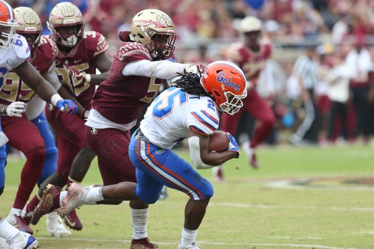 Florida Gators running back Jordan Scarlett (25) tries to fight off Florida State Seminoles linebacker Dontavious Jackson (5) as the Florida State Seminoles take on their rival the Florida Gators in college football at Doak S. Campbell Stadium, Saturday, Nov. 24, 2018.