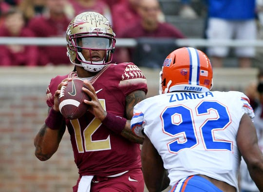 Nov 24, 2018; Tallahassee, FL, USA; Florida State Seminoles quarterback Deondre Francois (12) looks to throw as Florida Gators defensive lineman Jabari Zuniga (92) closes in during the first half at Doak Campbell Stadium. Mandatory Credit: Melina Myers-USA TODAY Sports