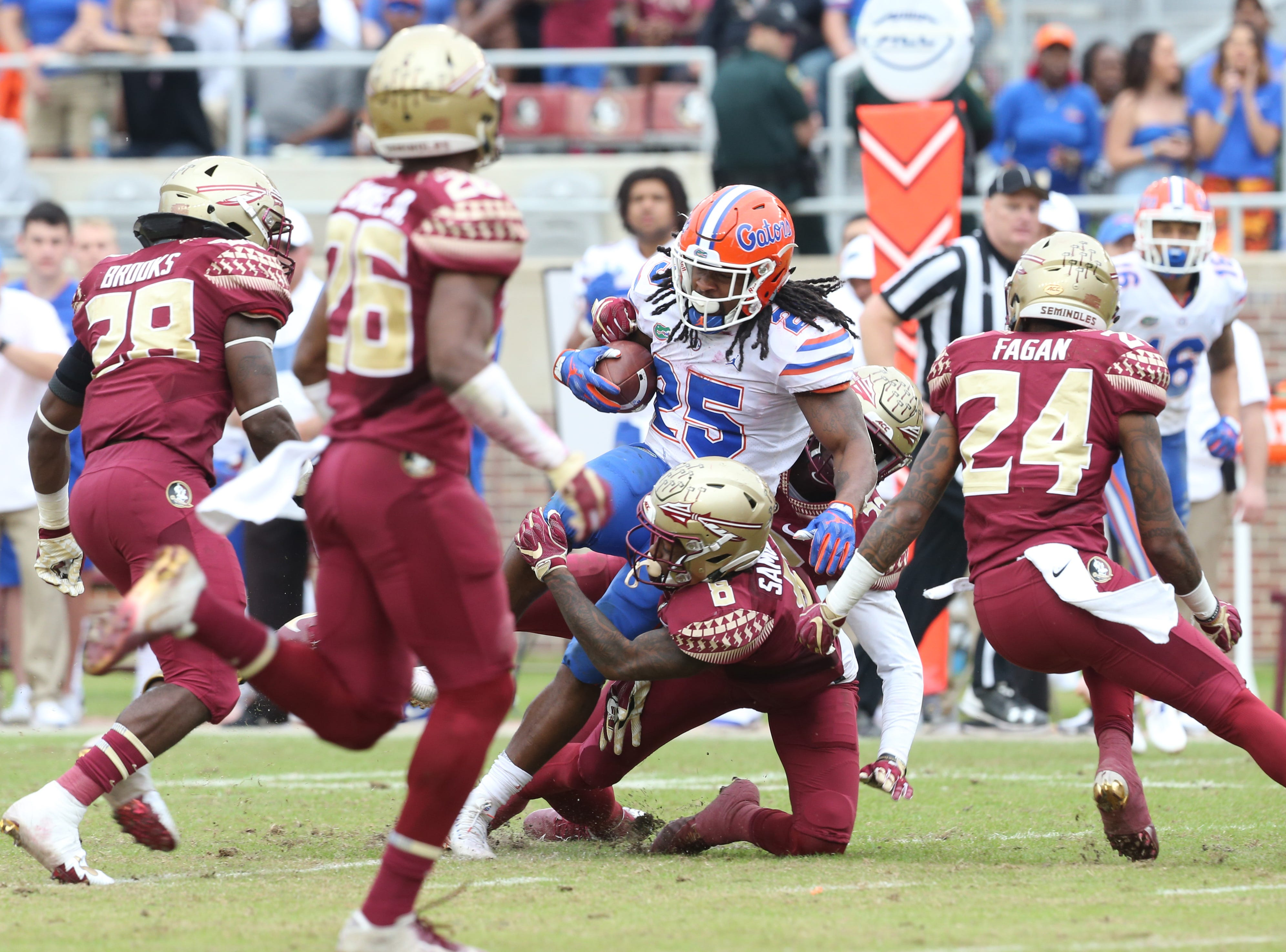 Florida Gators running back Jordan Scarlett (25) gets tackled by the Seminole defense as the Florida State Seminoles take on their rival the Florida Gators in college football at Doak S. Campbell Stadium, Saturday, Nov. 24, 2018.