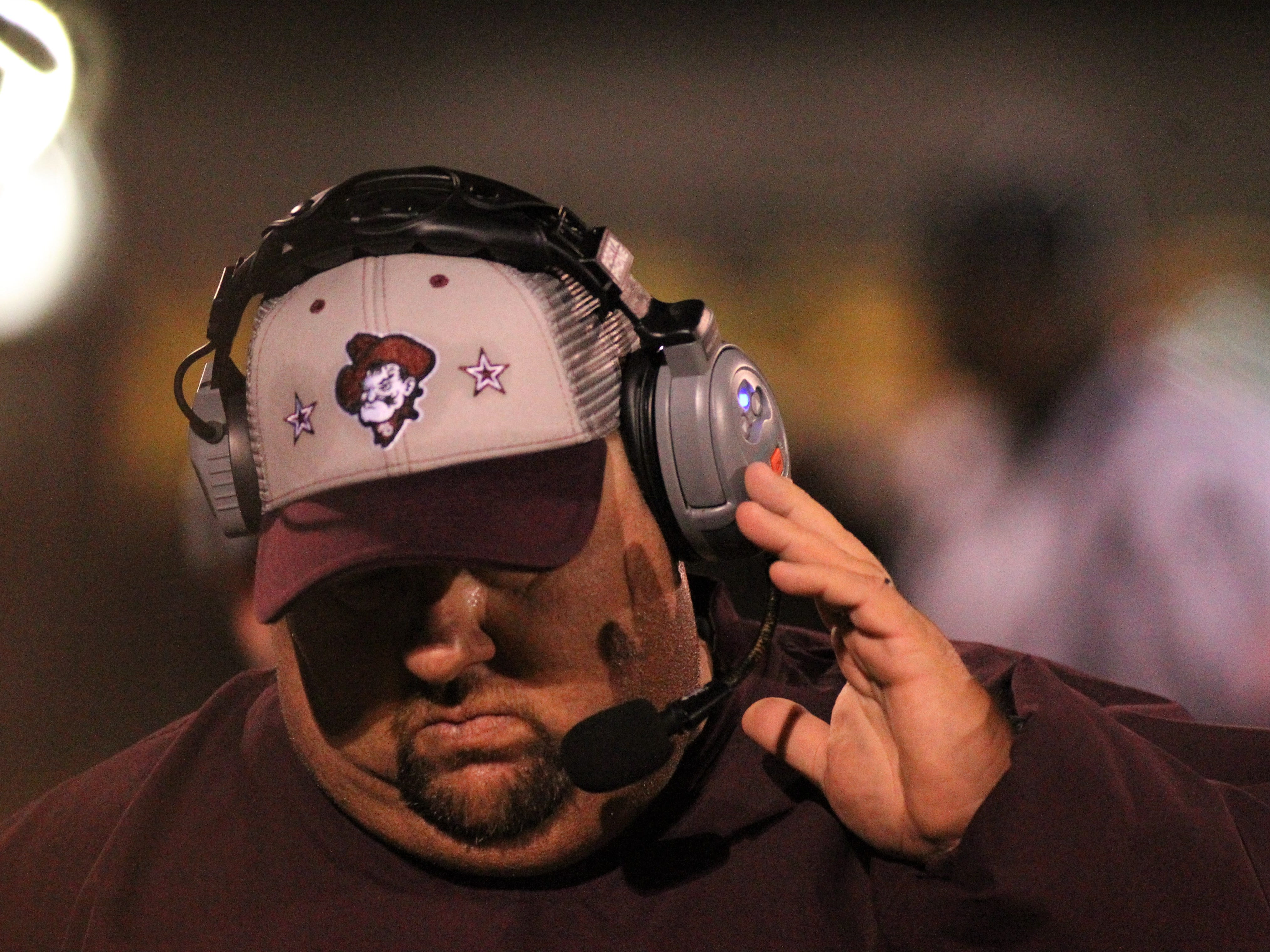 Madison County football coach Mike Coe talks to his coaches as the Cowboys beat Chiefland 49-14 in a Region 3-1A final at Boot Hill Stadium on Friday, Nov. 23, 2018.