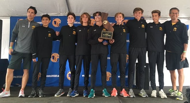 The Newbury Park High boys cross country team poses with the championship plaque after winning the Division 2 title Saturday.