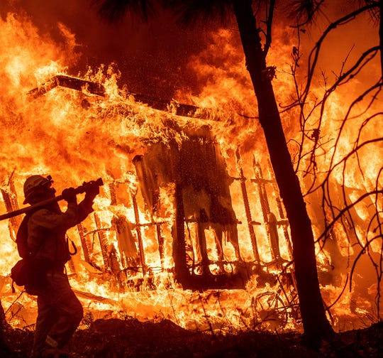 In this Nov. 9 photo, firefighter Jose Corona sprays water as flames from the Camp Fire consume a home in Magalia. A massive new federal report warns that extreme weather disasters like California's wildfires are worsening in the United States.