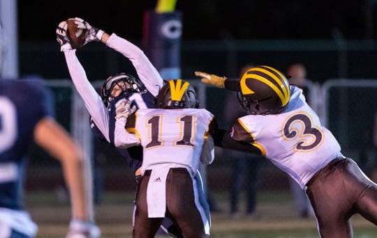 Central Valley Christian's Simon Tevelde takes a pass in the end zone under pressure from Golden West's Michael Wessel, right, and Jose Ramos in a Central Section Division IV championship high school football game on Friday, November 23, 2018.