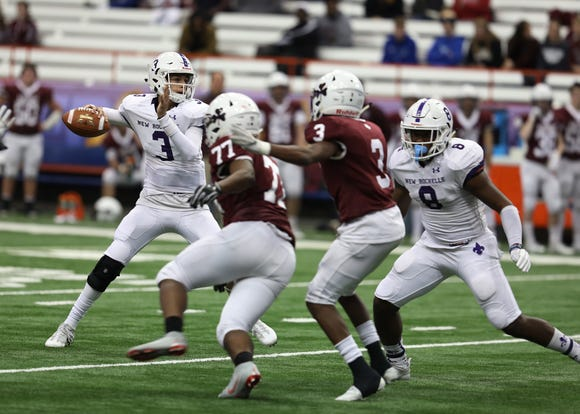 New Rochelle's QB Mac Coughlin gets off the pass before4 Aquinas's James Waters III and Damon Montgomery reach him during the Class A football championship game between Aquinas Institute and New Rochelle at the Carrier Dome in Syracuse on Nov. 24, 2018.