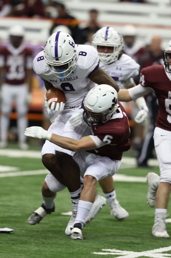 New Rochelle's Jordan Forrest is taken down by Aquinas's Ben Visca during the Class A football championship game between Aquinas Institute and New Rochelle at the Carrier Dome in Syracuse on Nov. 24, 2018.