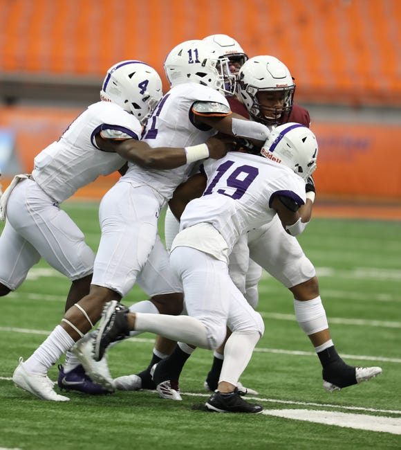 New Rochelle players Aaron Nelson, Khairi Manns, and Omari Walker stop Aquinas Ruben Torres during the Class A football championship game between Aquinas Institute and New Rochelle at the Carrier Dome in Syracuse on Nov. 24, 2018.