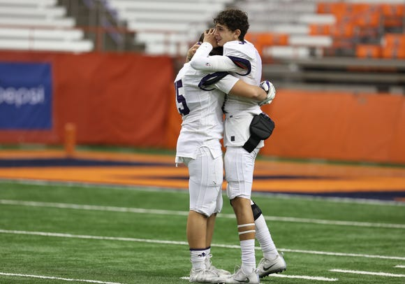 New Rochelle's Mac Coughlin comforts Vincent Ruggierio after their loss to Aquinas Institute 21-14 at the Carrier Dome in Syracuse on Nov. 24, 2018.