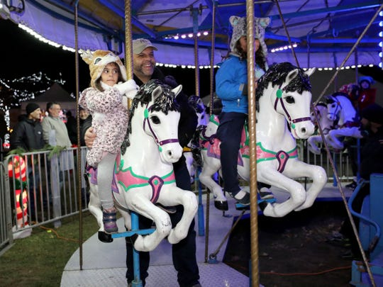 Daniela Terilli, 4, and Giancarlo Terilli from Pelham, ride a merry-go-round at the 5th annual Westchester's Winter Wonderland at Kensico Dam Plaza, Nov. 23, 2018.