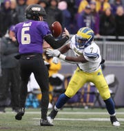 James Madison quarterback Ben DiNucci nearly loses the ball to Delaware defensive back Ray Jones in the first quarter at Bridgeforth Stadium during the opening round of the NCAA FCS playoffs Saturday.