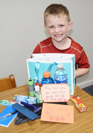 Hayden Hennessey, a first-grader from Saint Jo, Texas, gathers goodie bags with toiletry items for the homeless.
