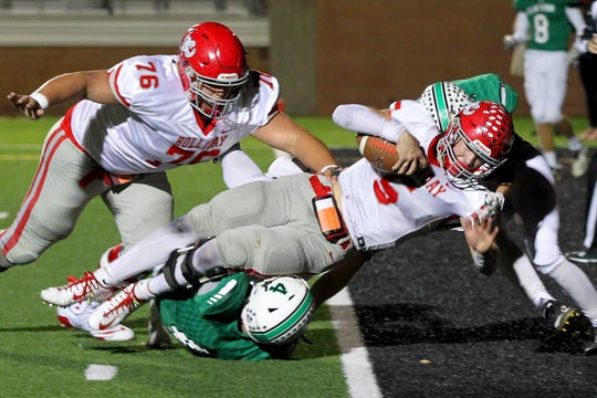 Holliday's Jett Johnson dives over the goal line to tie the game at 21-21 Friday night against Clifton.
