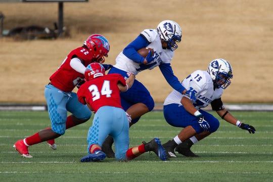 Gunnar Valverde and Reggie Jackson, junior, bring down Kendall Blue, senior quarterback. (Riley Fisher)