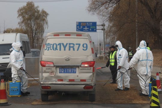 Workers disinfect passing vehicles in an area after the latest incident of African swine flu outbreak on the outskirts of Beijing, China, Friday, Nov. 23, 2018. Reeling from rising feed costs in Beijing's tariff fight with U.S. President Donald Trump, Chinese pig farmers face a new blow from an outbreak of African swine fever that has sent an economic shockwave through the countryside.