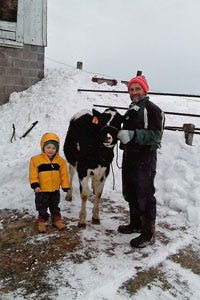 Max Tilderquest, then 2, stands beside his  calf, Seven, a Bolton daughter out of a Die-Hard daughter, donated by  Bob Traynor (right) of Honeycrest Farms in Spring Valley, Wisconsin.