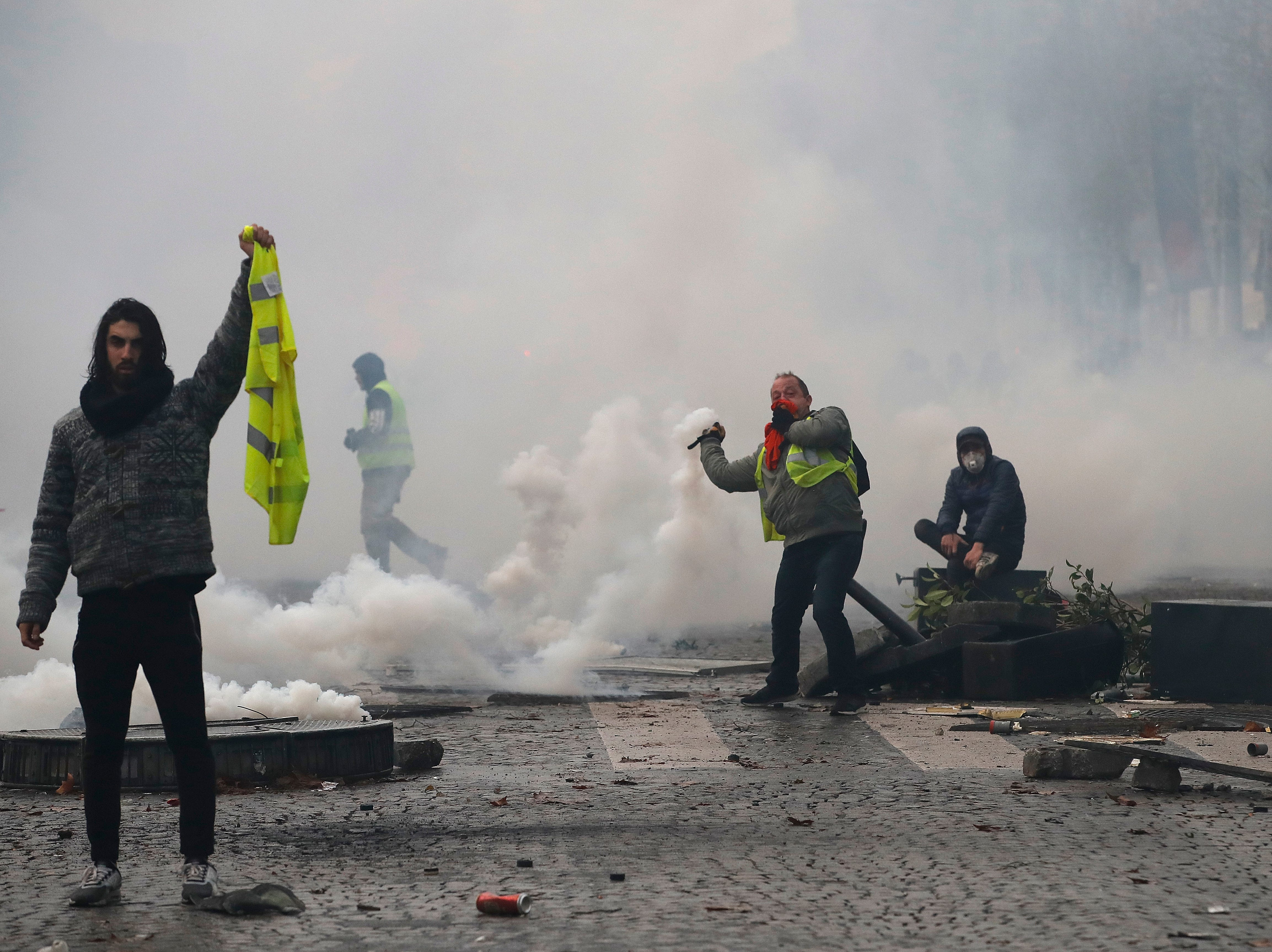 A demonstrator shows his yellow jacket while another one throws a gas canister during a protest against the rising of the fuel taxes, on the Champs-Elysees avenue, Saturday, Nov. 24, 2018 in Paris.