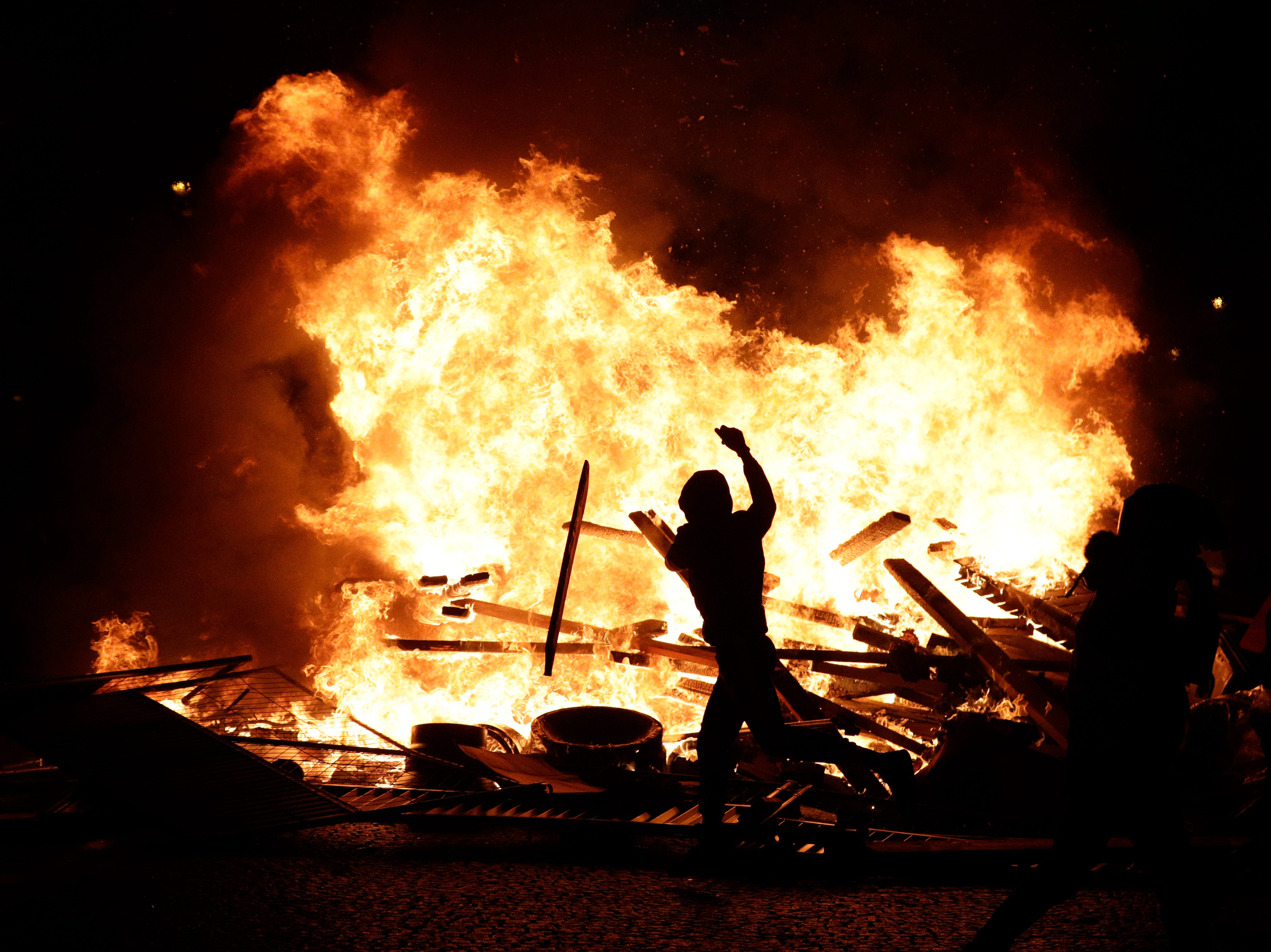 A demonstrator throws debris at a burning barricade while protesting with others against the rising of the fuel taxes on the famed Champs Elysees avenue, in Paris, France, Saturday, Nov. 24, 2018.