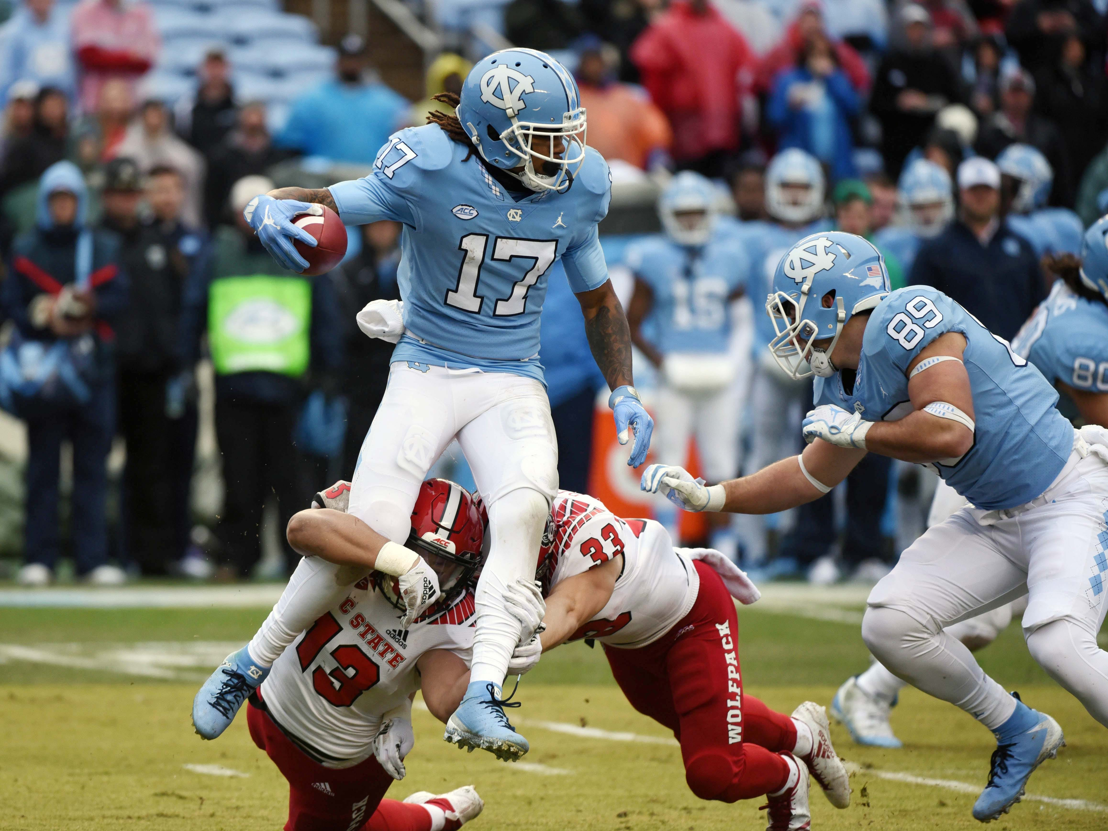 North Carolina Tar Heels receiver Anthony Ratliff-Williams (17) is tackled by North Carolina State Wolfpack defender Stephen Morrison (13) during the first half at Kenan Memorial Stadium.