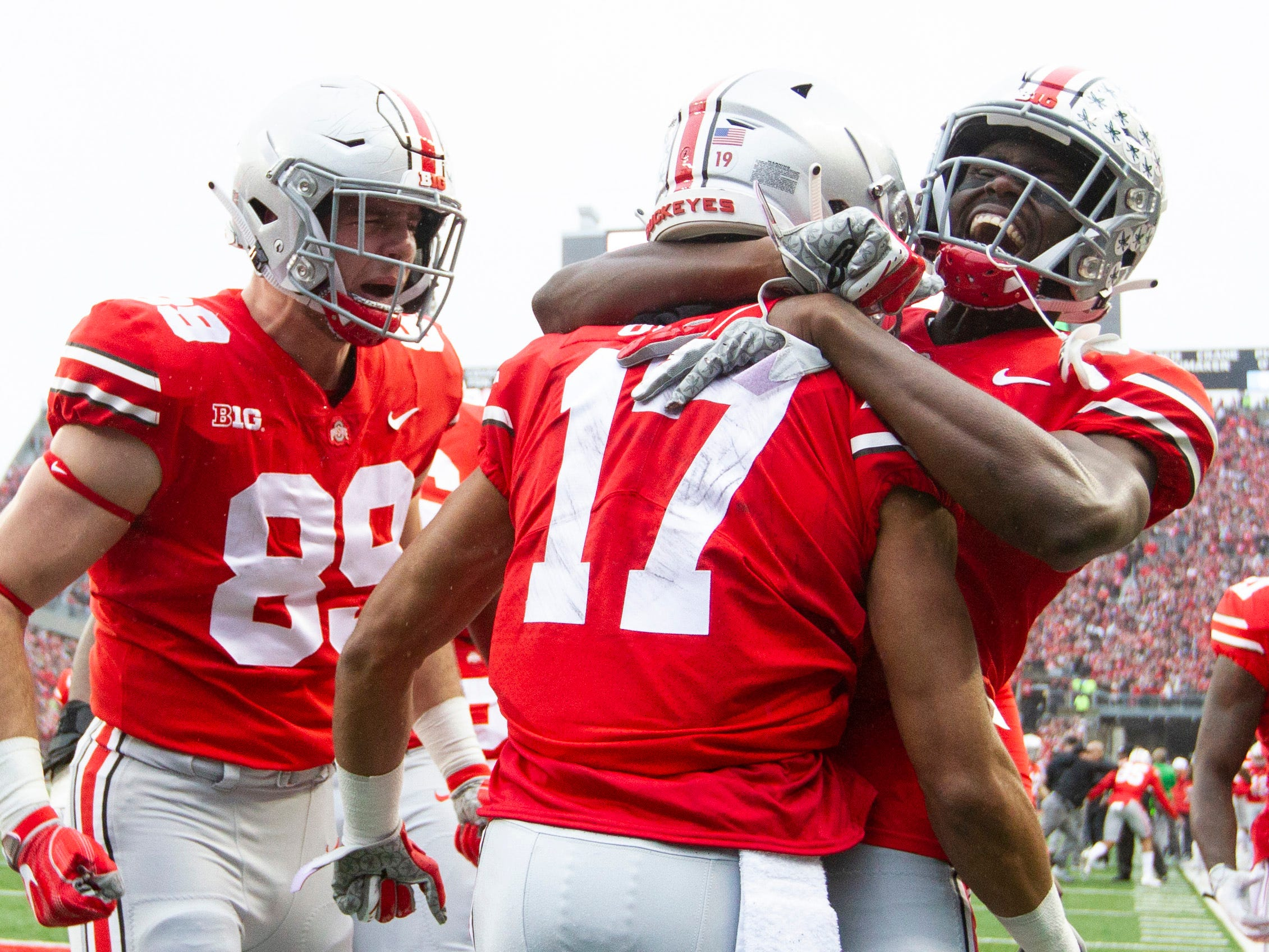 Ohio State Buckeyes wide receiver Chris Olave (17) is congratulated by tight end Luke Farrell (89) and wide receiver Binjimen Victor (9) after scoring a first-quarter touchdown against the Michigan Wolverines at Ohio Stadium.