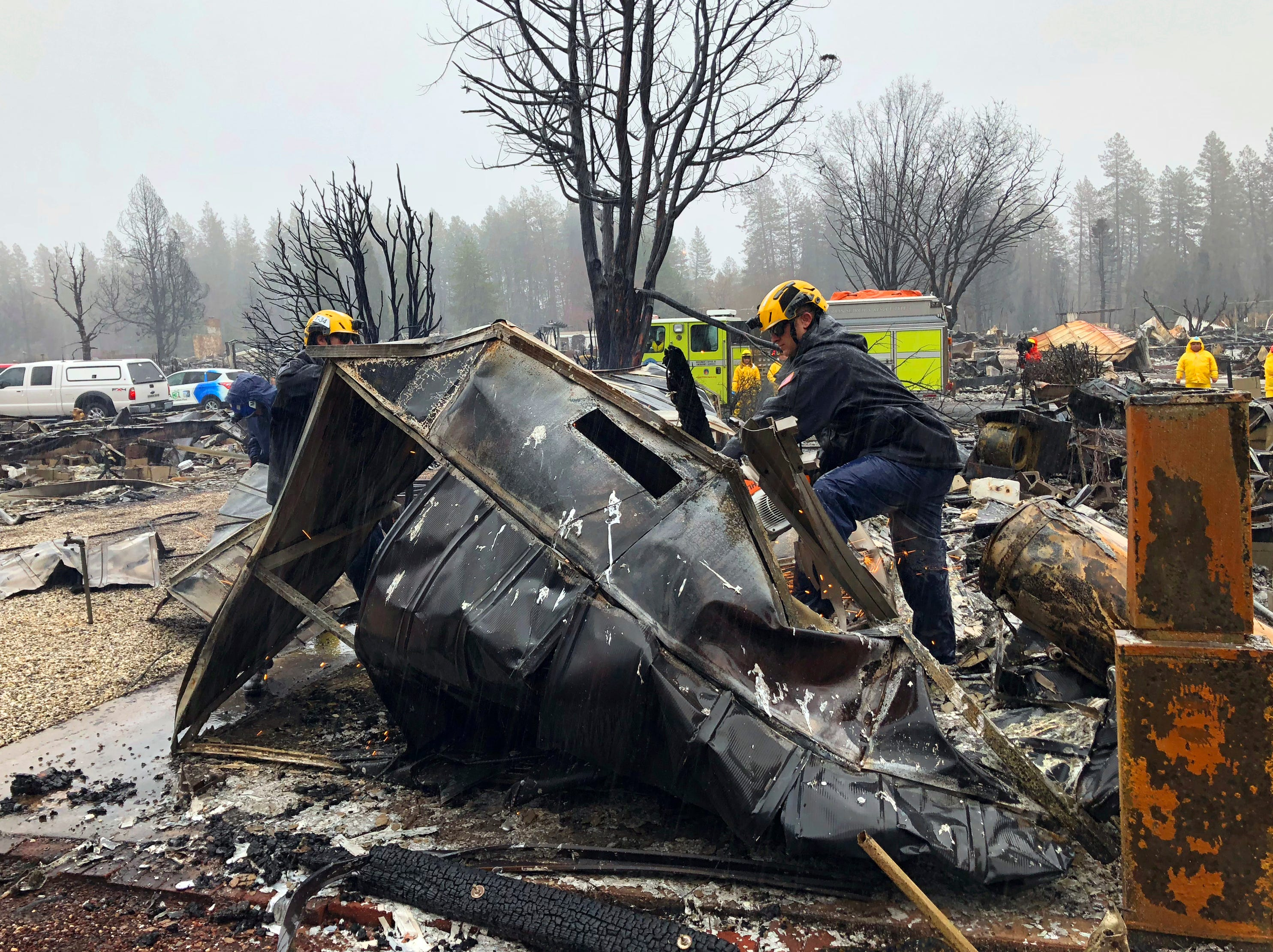 Steven McKnight, right, and Daniel Hansen saw through large pieces of sheet metal so they can be moved to allow cadaver dogs to search beneath them for signs of human remains at a mobile home park in Paradise, Calif., Friday, Nov. 23, 2018. They said the mobile home park had already been hand searched, so they were re-examining it with search dogs.
