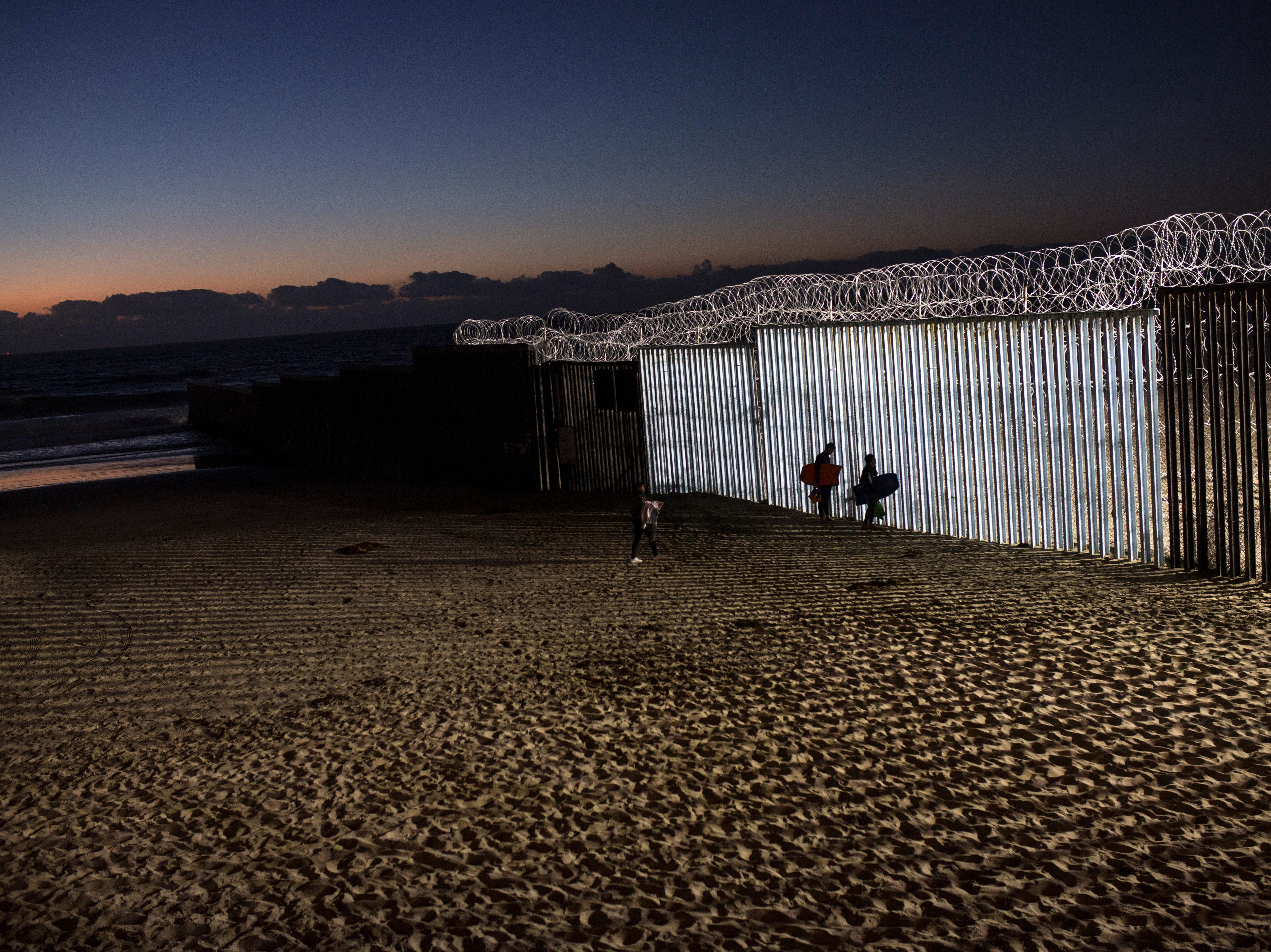 Bodyboarders walk next to the U.S.-Mexico border structure in Tijuana, Mexico, Friday, Nov. 23, 2018. The mayor of Tijuana has declared a humanitarian crisis in his border city and says that he has asked the United Nations for aid to deal with the approximately 5,000 Central American migrants who have arrived in the city.3