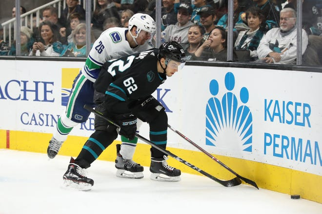 Vancouver Canucks left wing Antoine Roussel, left, had 18 penalty minutes Friday night against the San Jose Sharks.