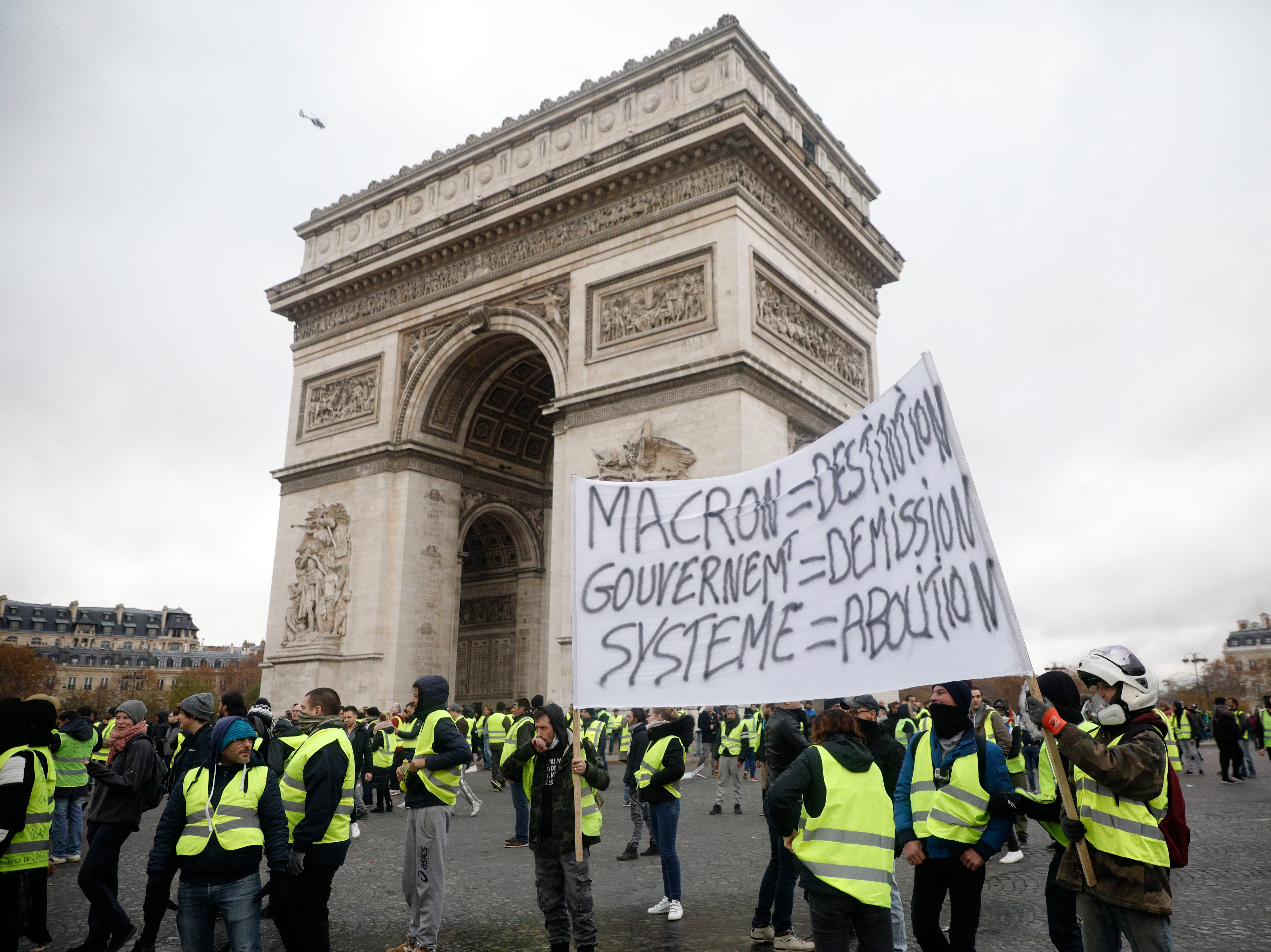 Demonstrators, called the yellow jackets, gather around the Arc de Triomphe as they protest against the fuel taxes, in Paris, France, Saturday, Nov. 24, 2018.