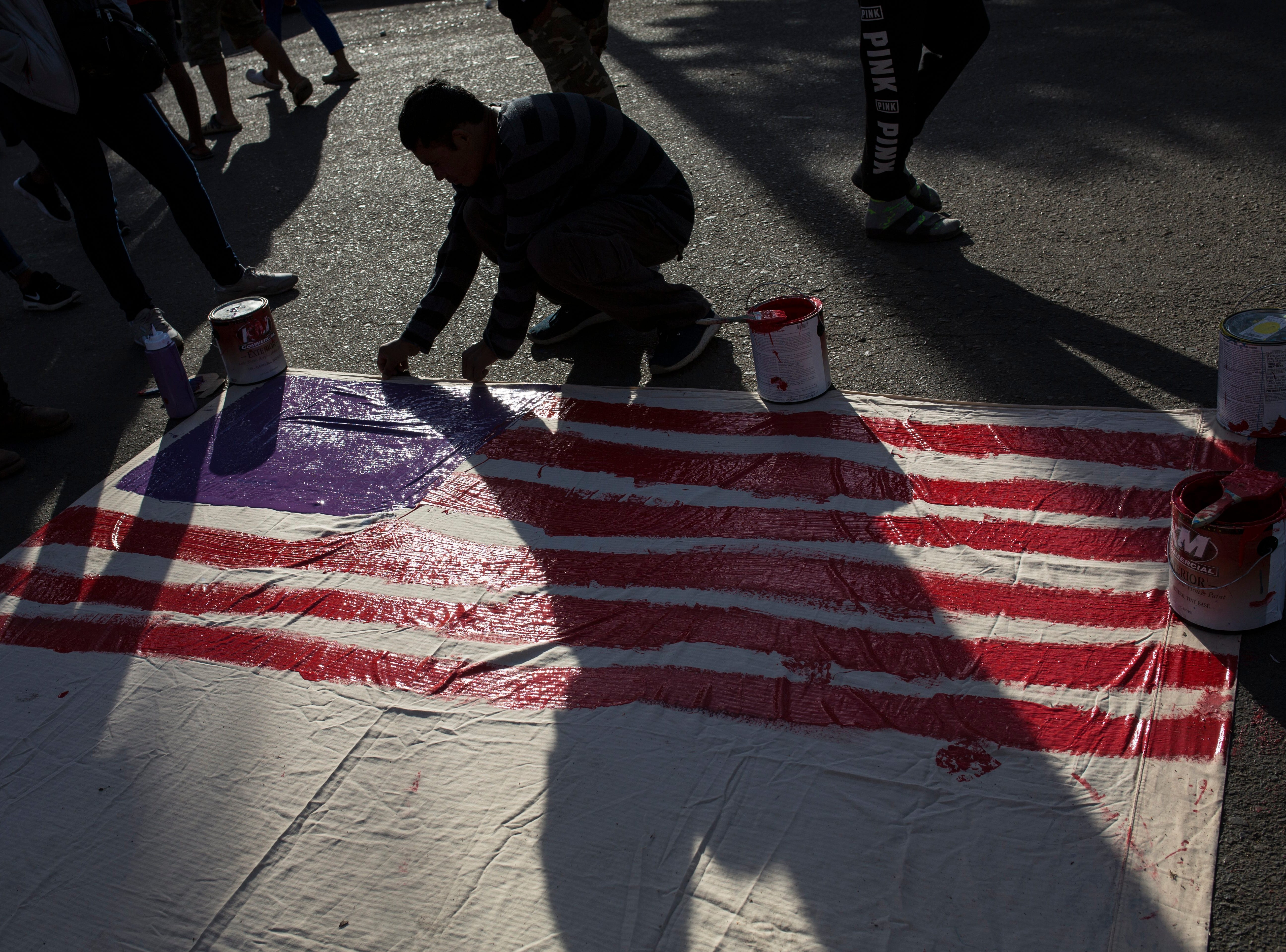 A man paints a sign with the U.S. flag outside a migrant shelter in Tijuana, Mexico, Friday, Nov. 23, 2018.