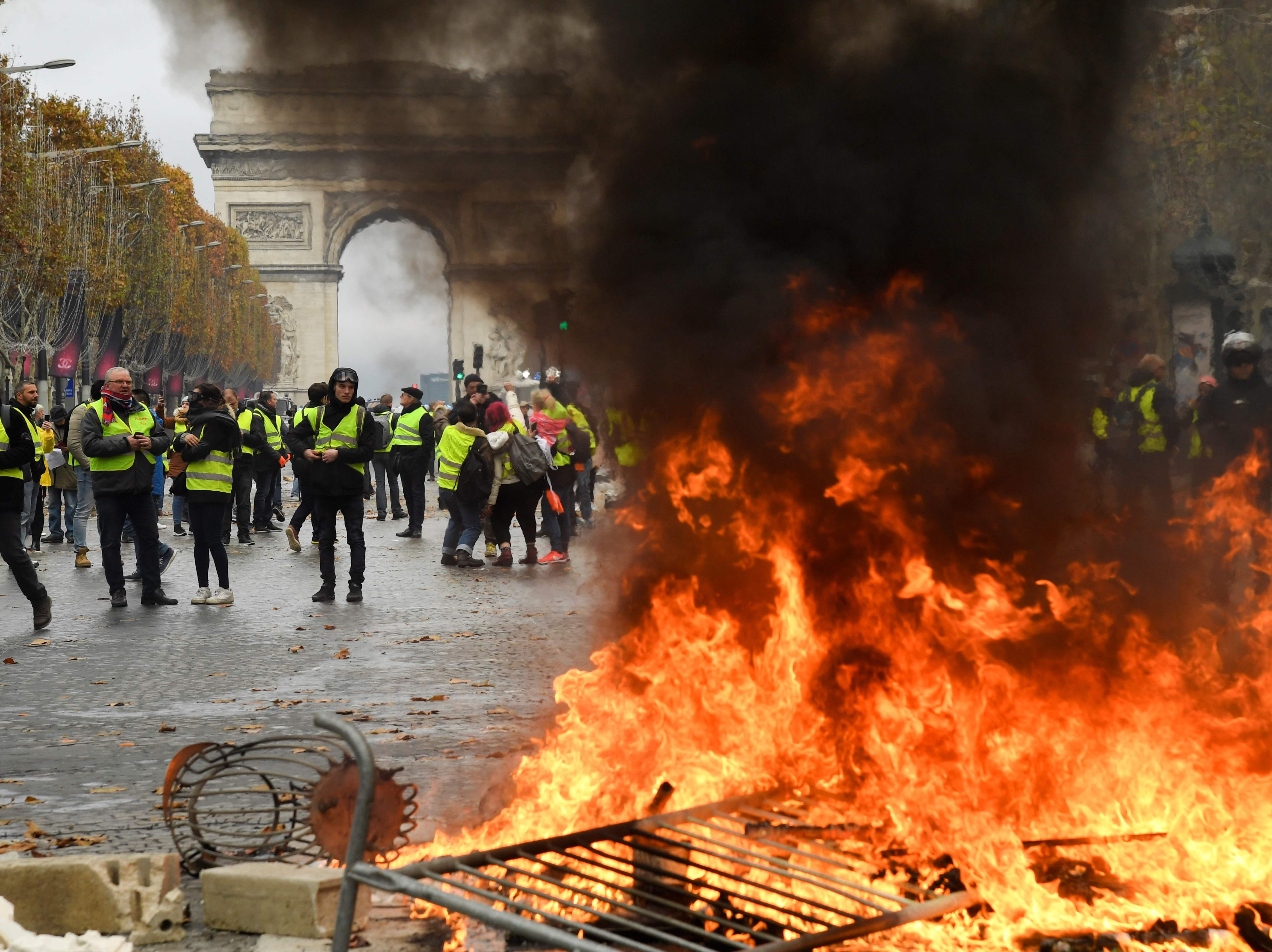 Protestors stand in front of a fire of furnitures during a protest of Yellow vests against rising oil prices and living costs near the Arc of Triomphe on the Champs Elysees in Paris, on Nov. 24, 2018.