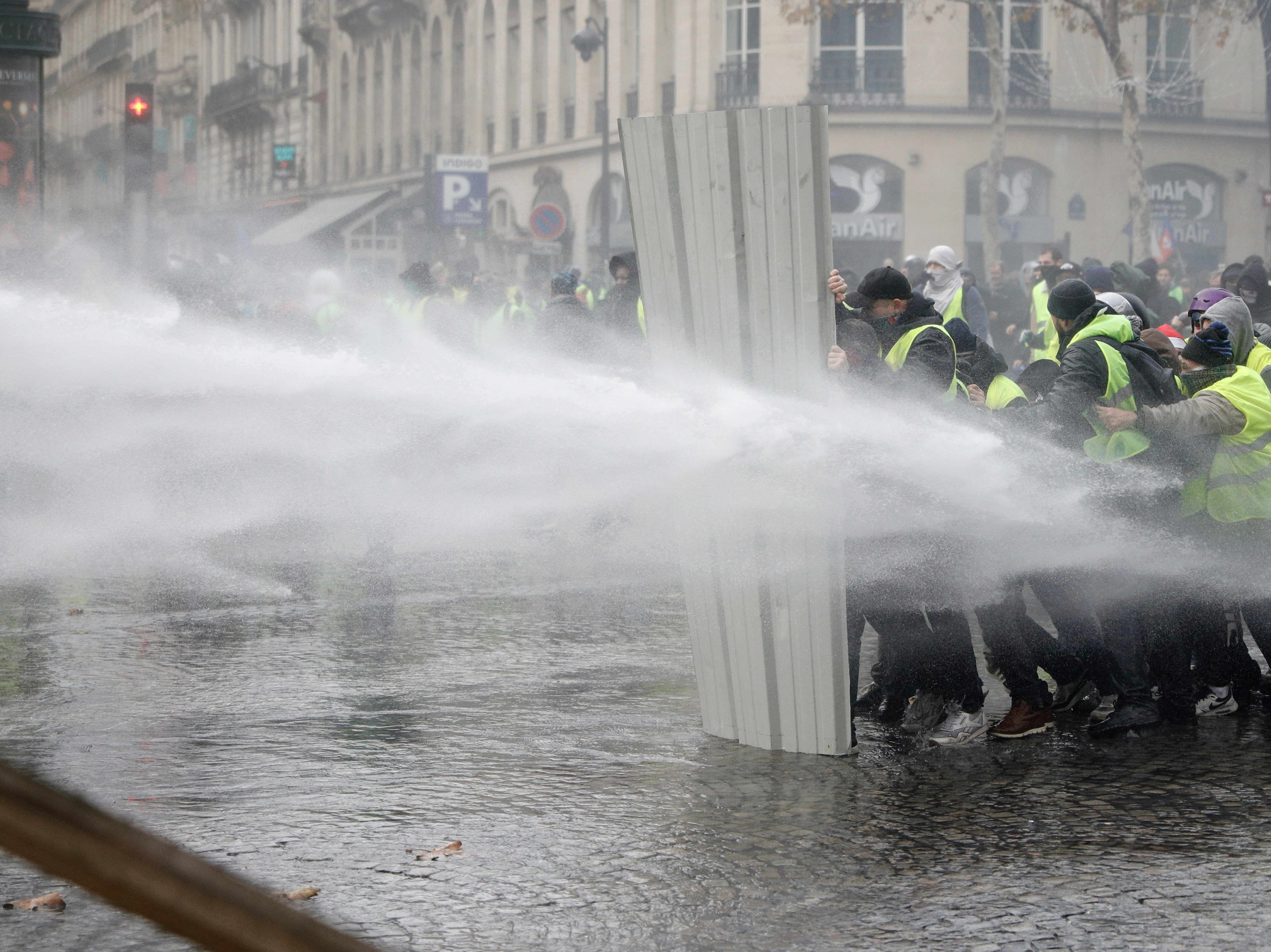 Demonstrators, called the yellow jackets, use a construction barrier to repel a police water canon, during clashes on the famed Champs-Elysees avenue in Paris, France, as they protest against the rising of the fuel taxes, Saturday, Nov. 24, 2018.