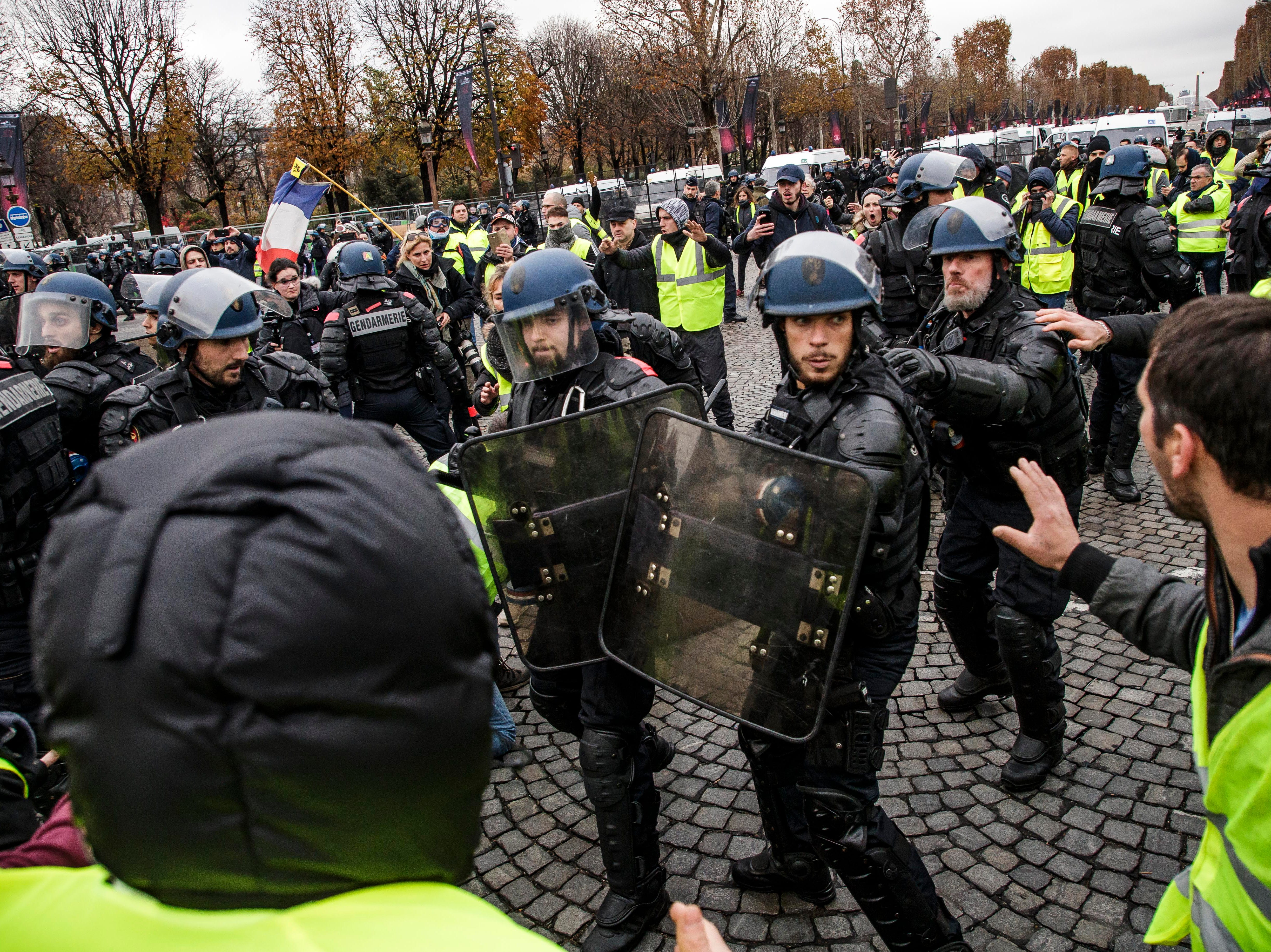 Police forces stop people wearing yellow vests, as a symbol of French driver's and citizen's protest against higher fuel prices, during a demonstration on the Champs Elysee as part of a nationwide protest in Paris, France on Nov. 24, 2018. The so-called 'gilets jaunes' (yellow vests) protest movement, which has reportedly no political affiliation, is protesting over fuel prices.