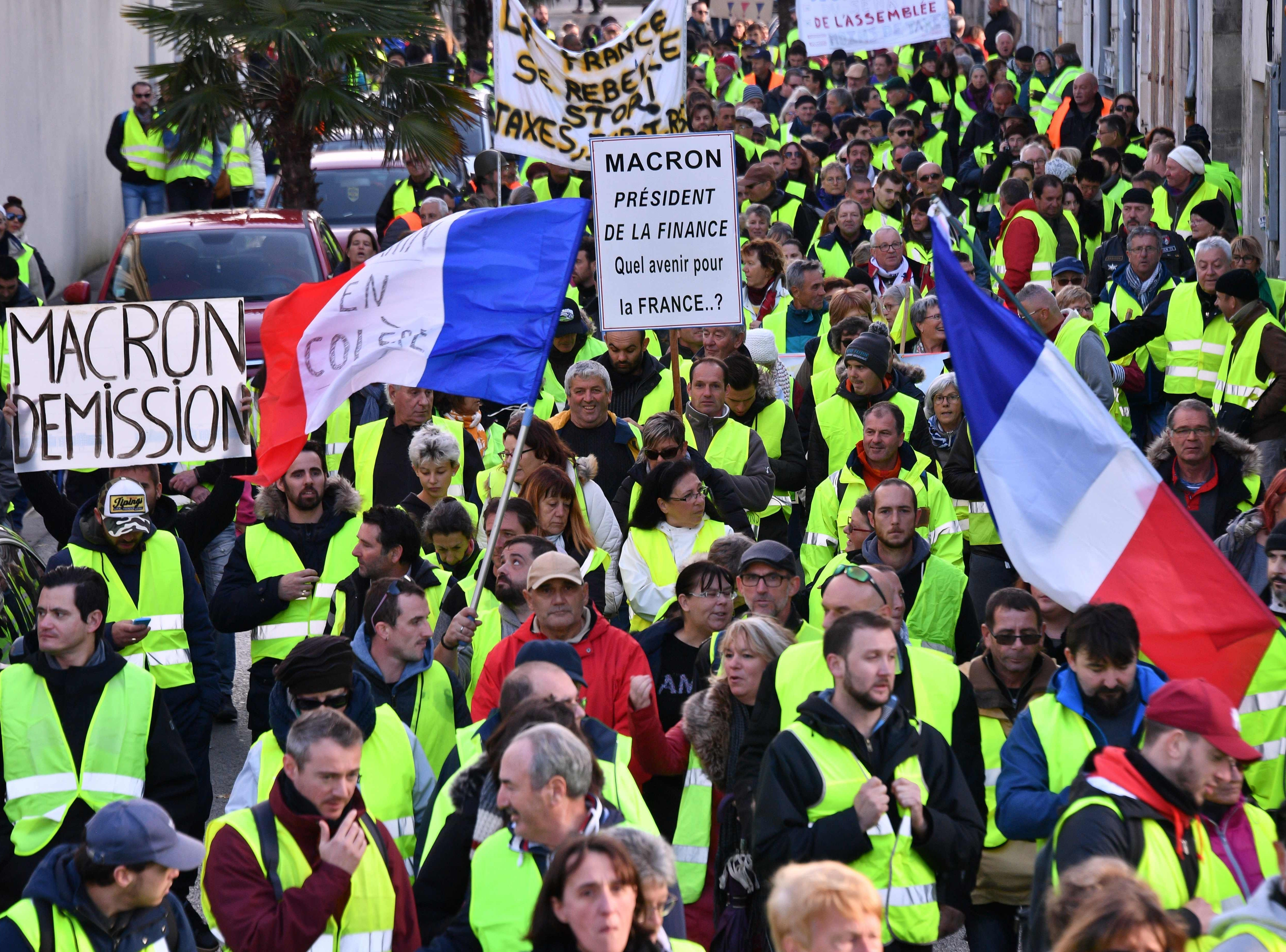 Yellow Vests (Gilets jaunes) shout slogans and wave placards as they participate in a protest rally against high fuel prices in Rochefort, south-western France on Nov. 24, 2018, part of a movement  which has mushroomed into a widespread protest against stagnant spending power under the French President. The demonstrations were sparked by an increase in diesel tax, justified as an anti-pollution levy by the government but have morphed into a broad opposition front to centrist Macron.