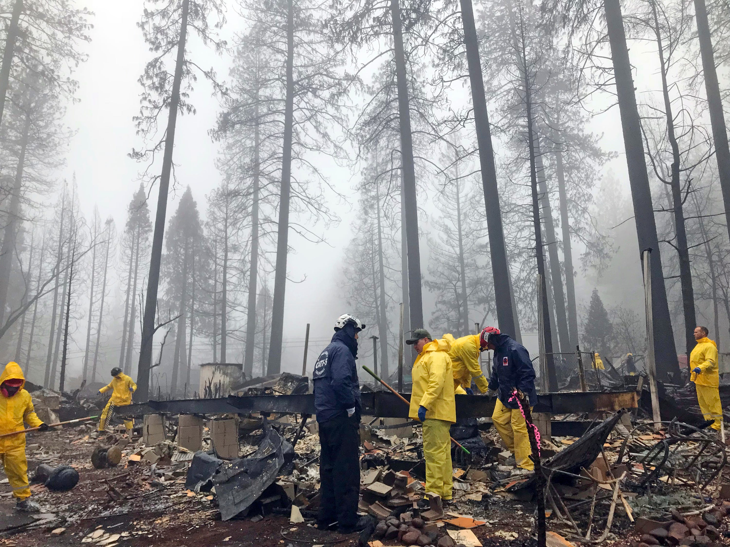 After a brief delay to let a downpour pass, volunteers resume their search for human remains at a mobile home park in Paradise, Calif., Friday, Nov. 23, 2018. A team from Orange County in Southern California is among several teams conducting a second search of a mobile home park after the deadly Camp wildfire torched part of Butte County in Northern California. Task force leader Craig Covey, in blue jacket at center, says his team is doing a second search because there are outstanding reports of missing people whose last known address was at the mobile home park.
