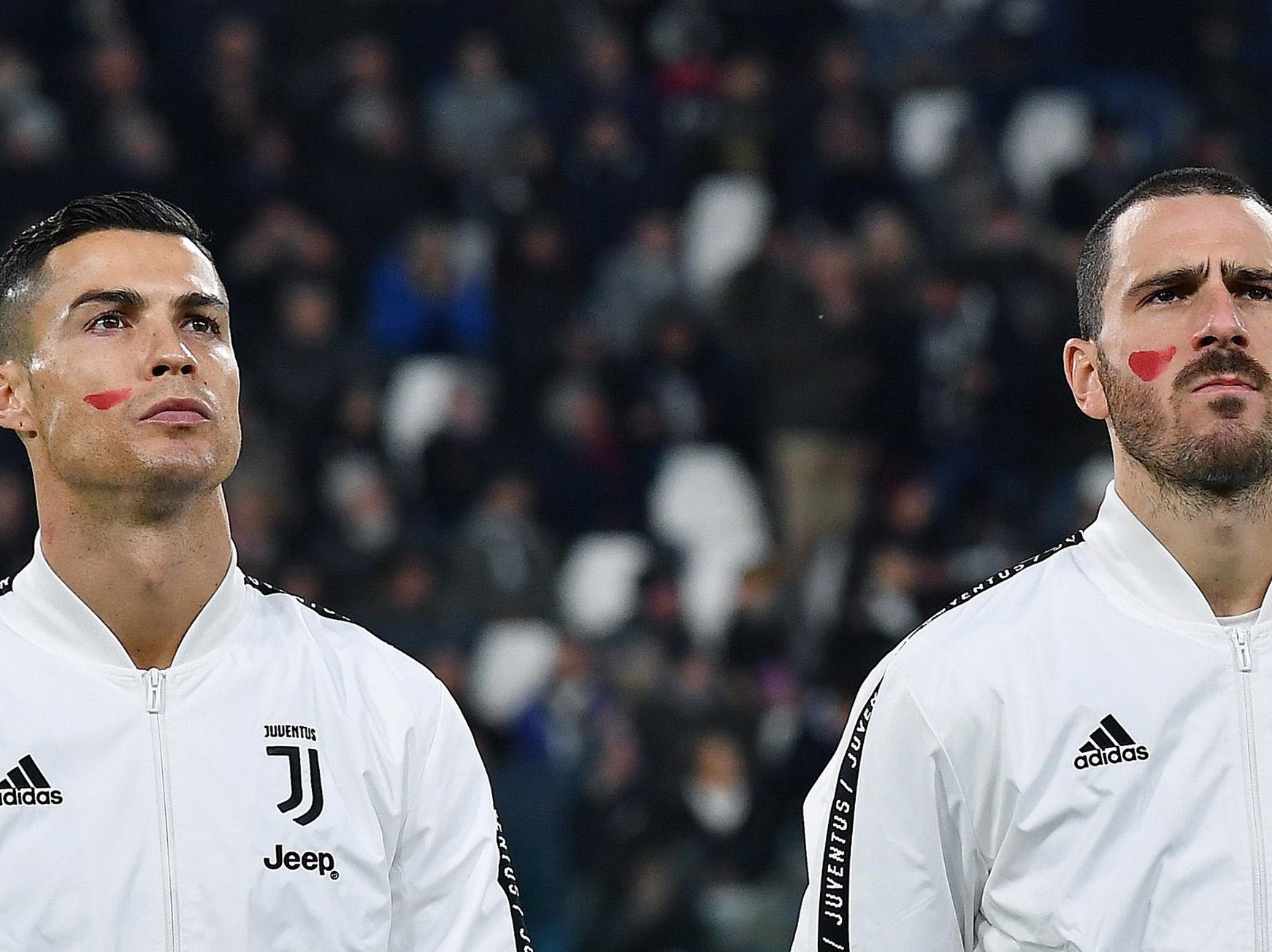 Juventus' players Leonardo Bonucci, right, and Cristiano Ronaldo wear a red sign on their faces on the occasion of the day against violence against women before the Italian Serie A soccer match Juventus FC vs Spal at the Allianz stadium in Turin, Italy on Nov. 24, 2018.