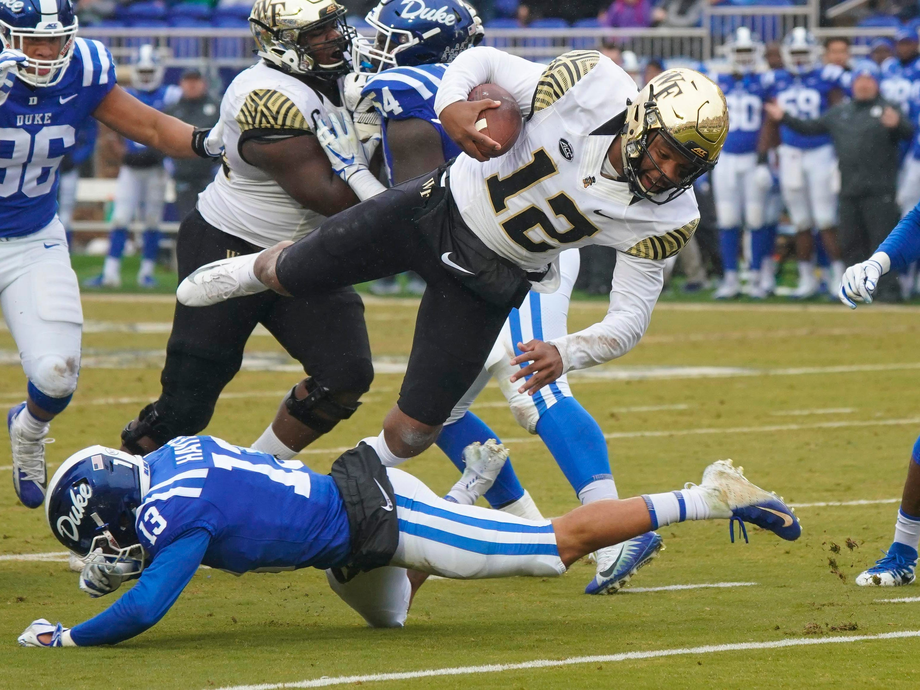 Wake Forest Demon Deacons quarterback Jamie Newman (12) is stopped on his run by Duke Blue Devils safety Jordan Hayes (13) during the first half at Wallace Wade Stadium.