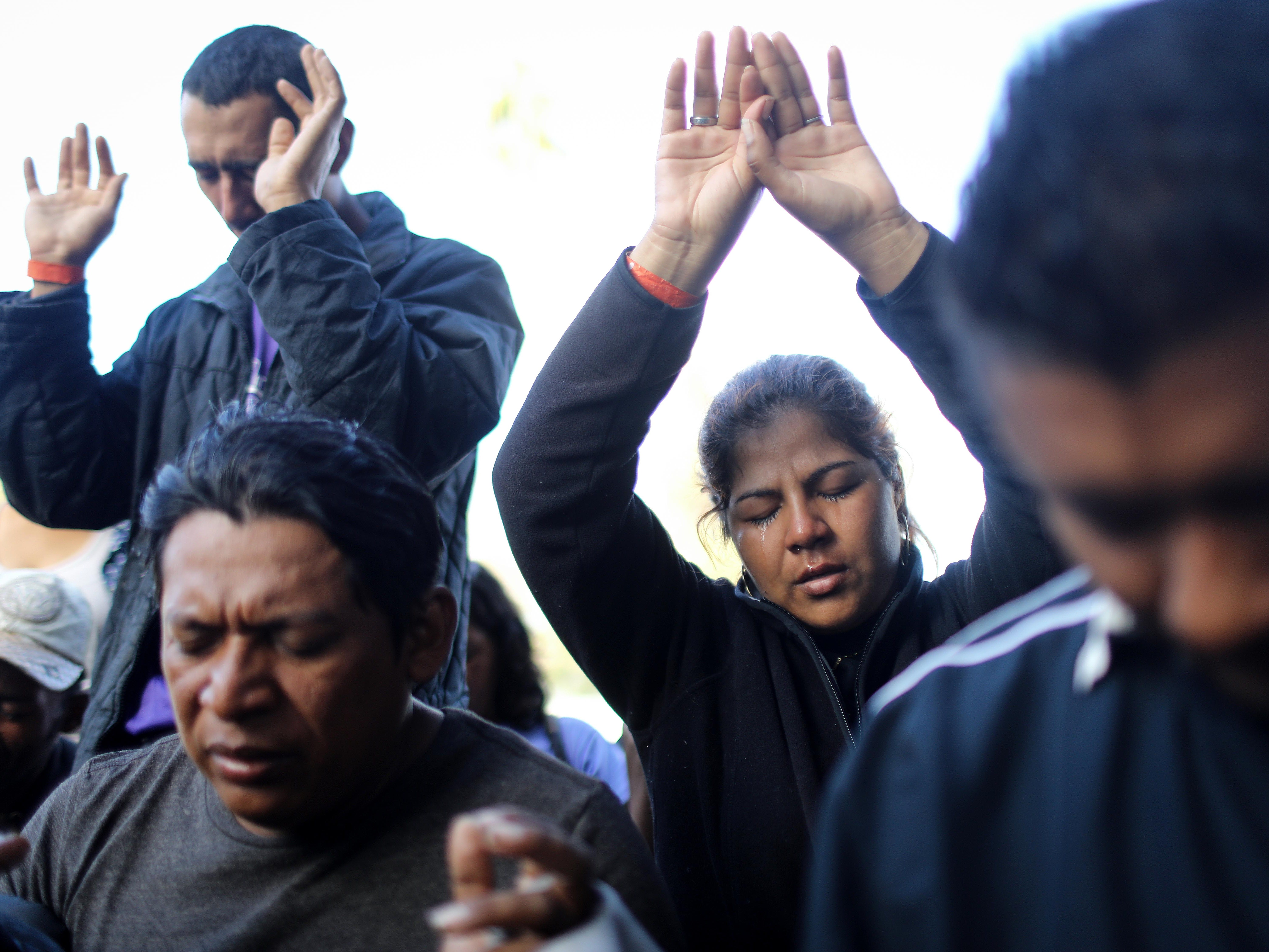 Members of the 'migrant caravan' worship during a street worship service outside a temporary shelter set up for members of the caravan on Nov. 23, 2018 in Tijuana, Mexico.