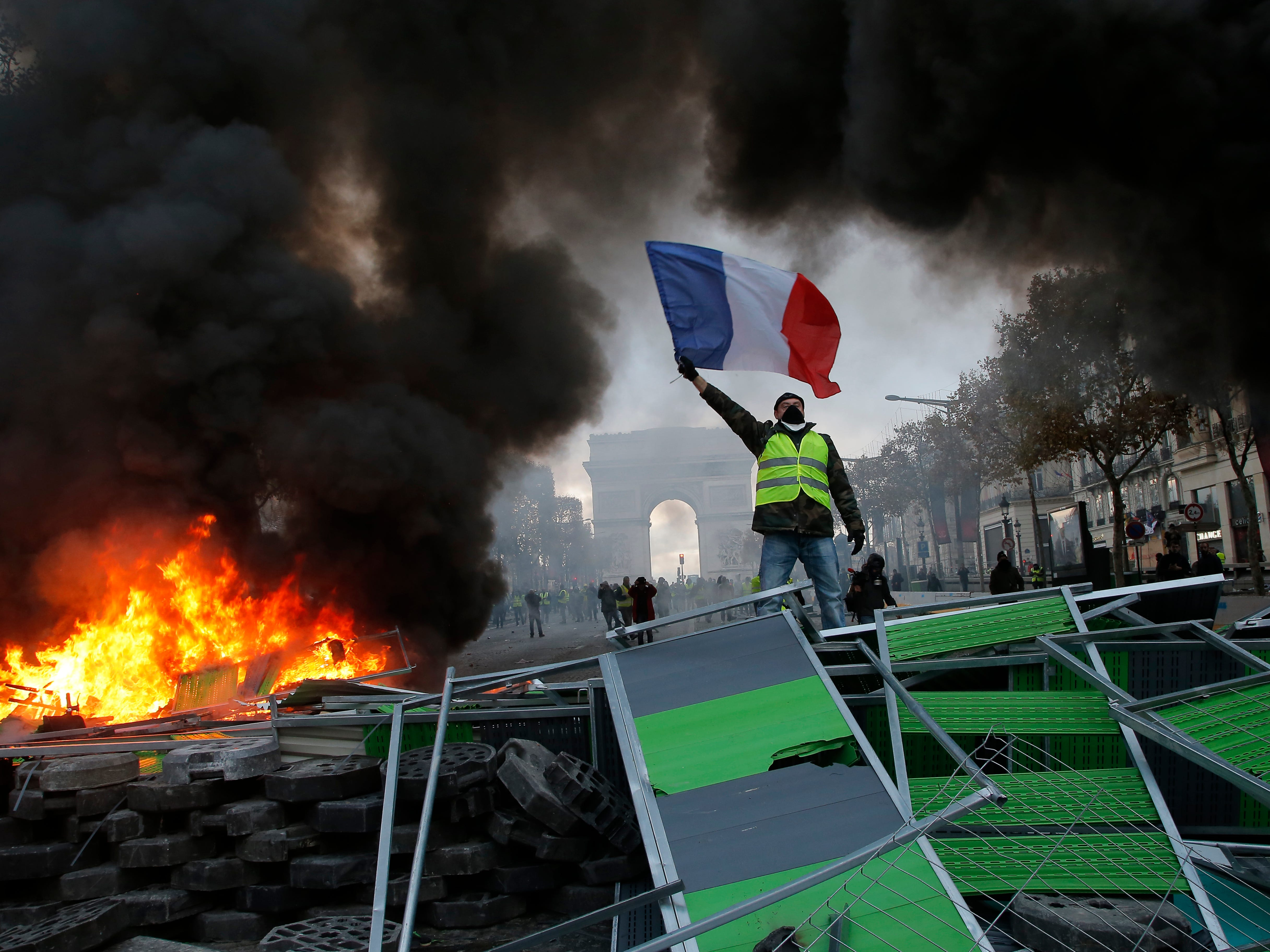 A demonstrator waves the French flag onto a burning barricade on the Champs-Elysees avenue during a demonstration against the rising of the fuel taxes, Saturday, Nov. 24, 2018 in Paris.