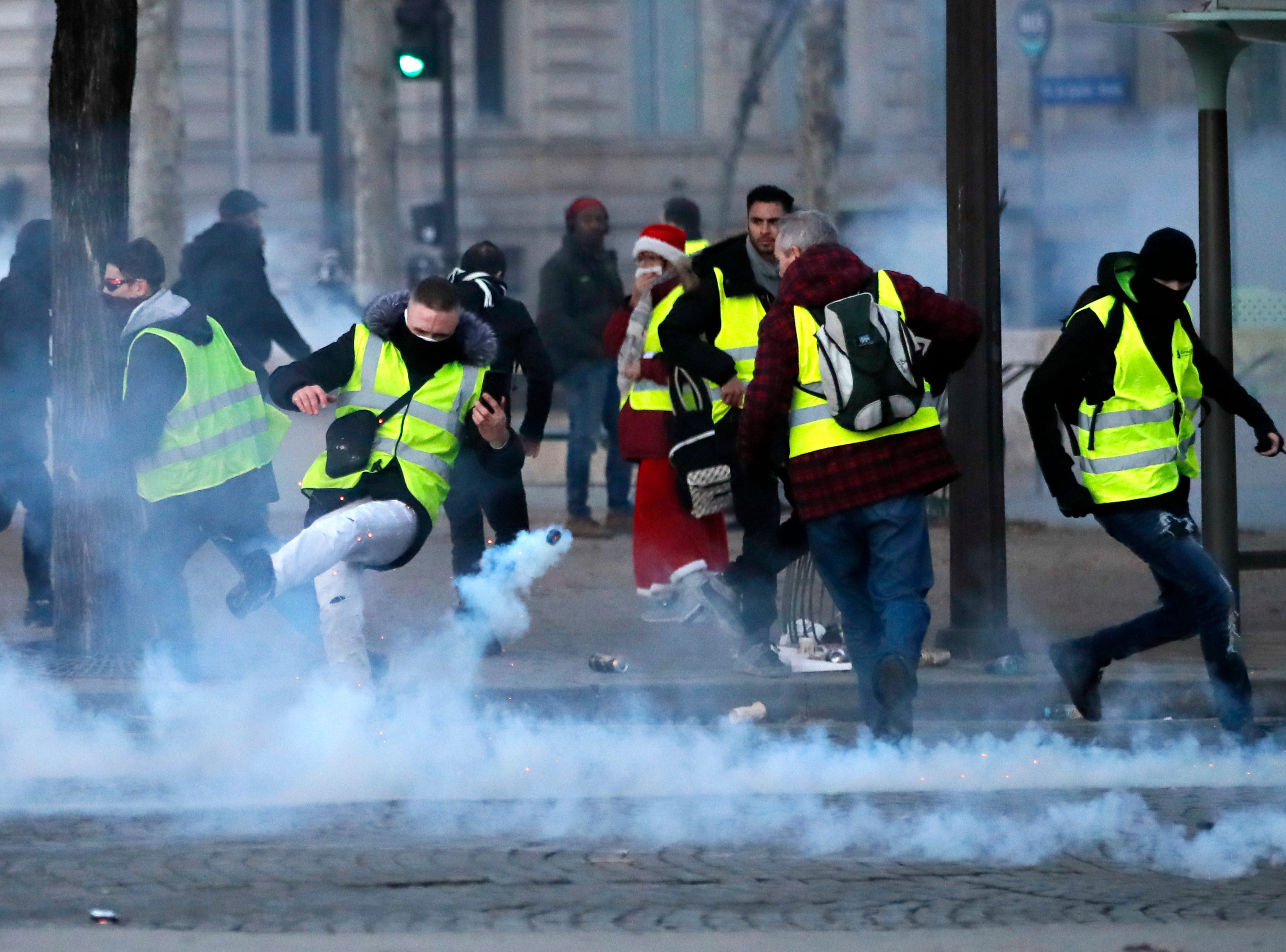 A demonstrator wearing a yellow jacket kicks in a tear gas canister on the Champs-Elysees avenue, during a protest against tax Saturday, Nov. 24, 2018 in Paris.
