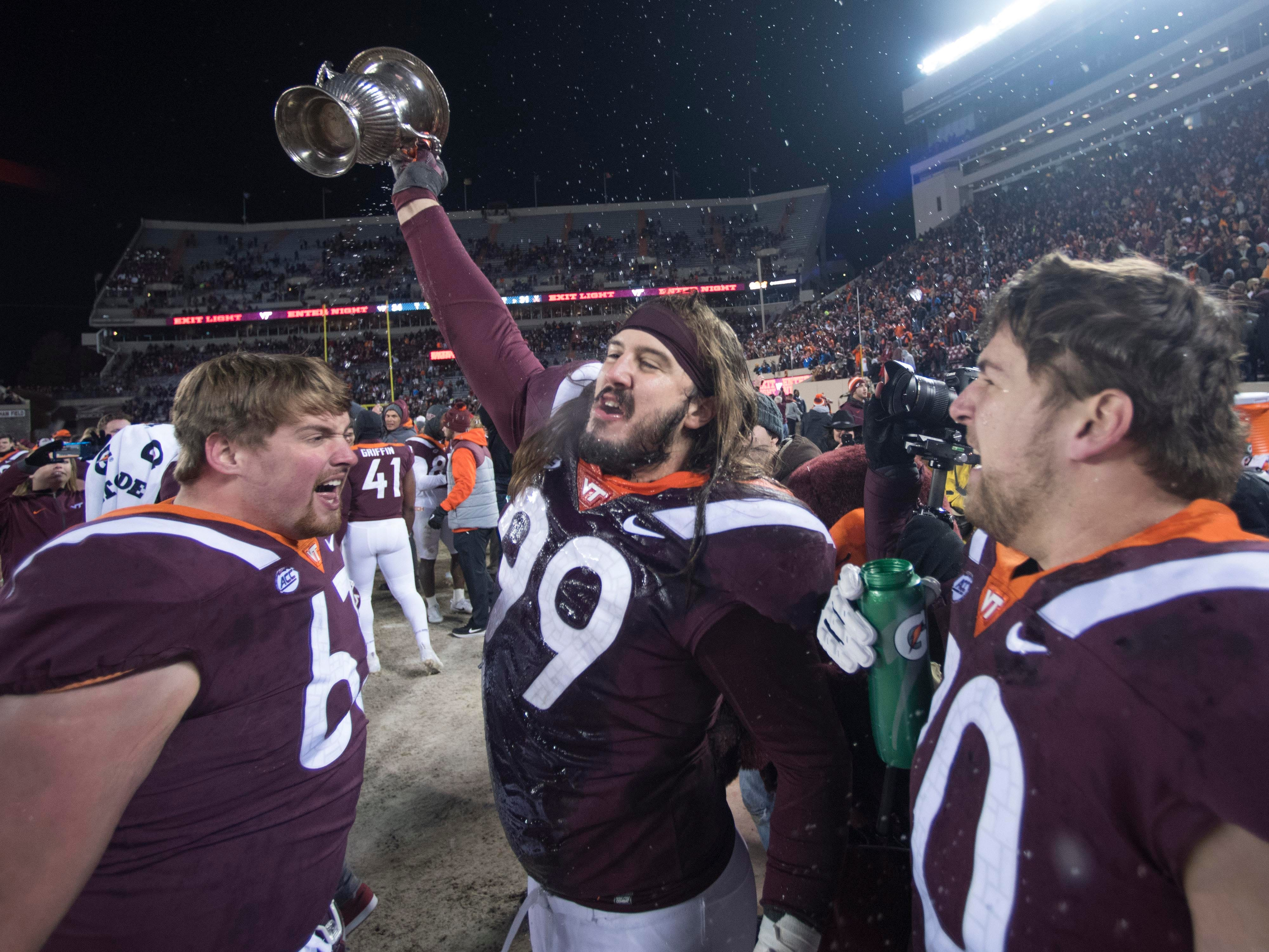 Virginia Tech defensive lineman Vinny Mihota raises the Commonwealth Cup along side his teammates after defeating rival Virginia in overtime.