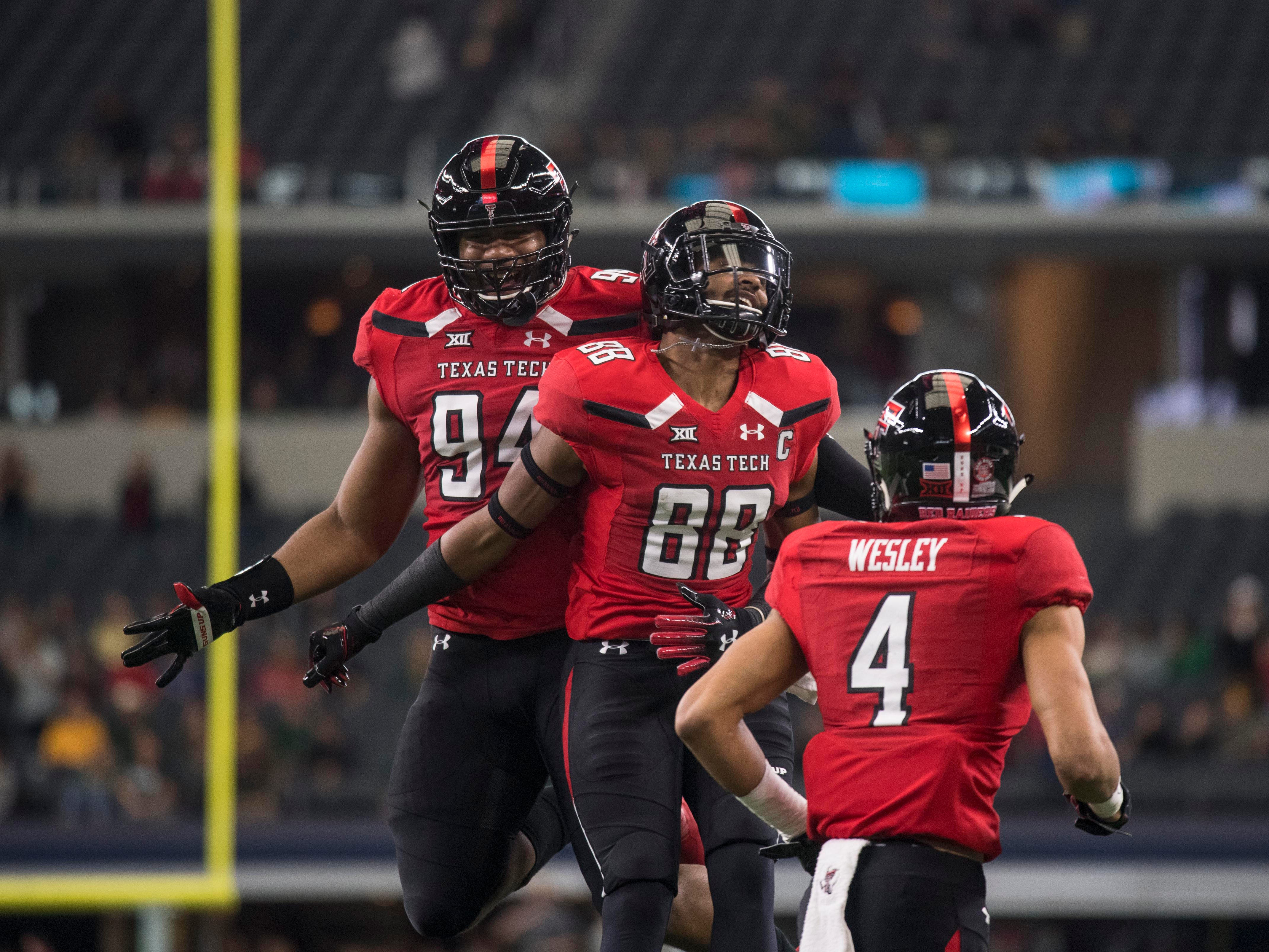 Nov 24, 2018; Arlington, TX, USA; Texas Tech Red Raiders defensive lineman Lonzell Gilmore (94), wide receiver Ja'Deion High (88) and wide receiver Antoine Wesley (4) celebrate a touchdown against the Baylor Bears during the first quarter at AT&T Stadium.