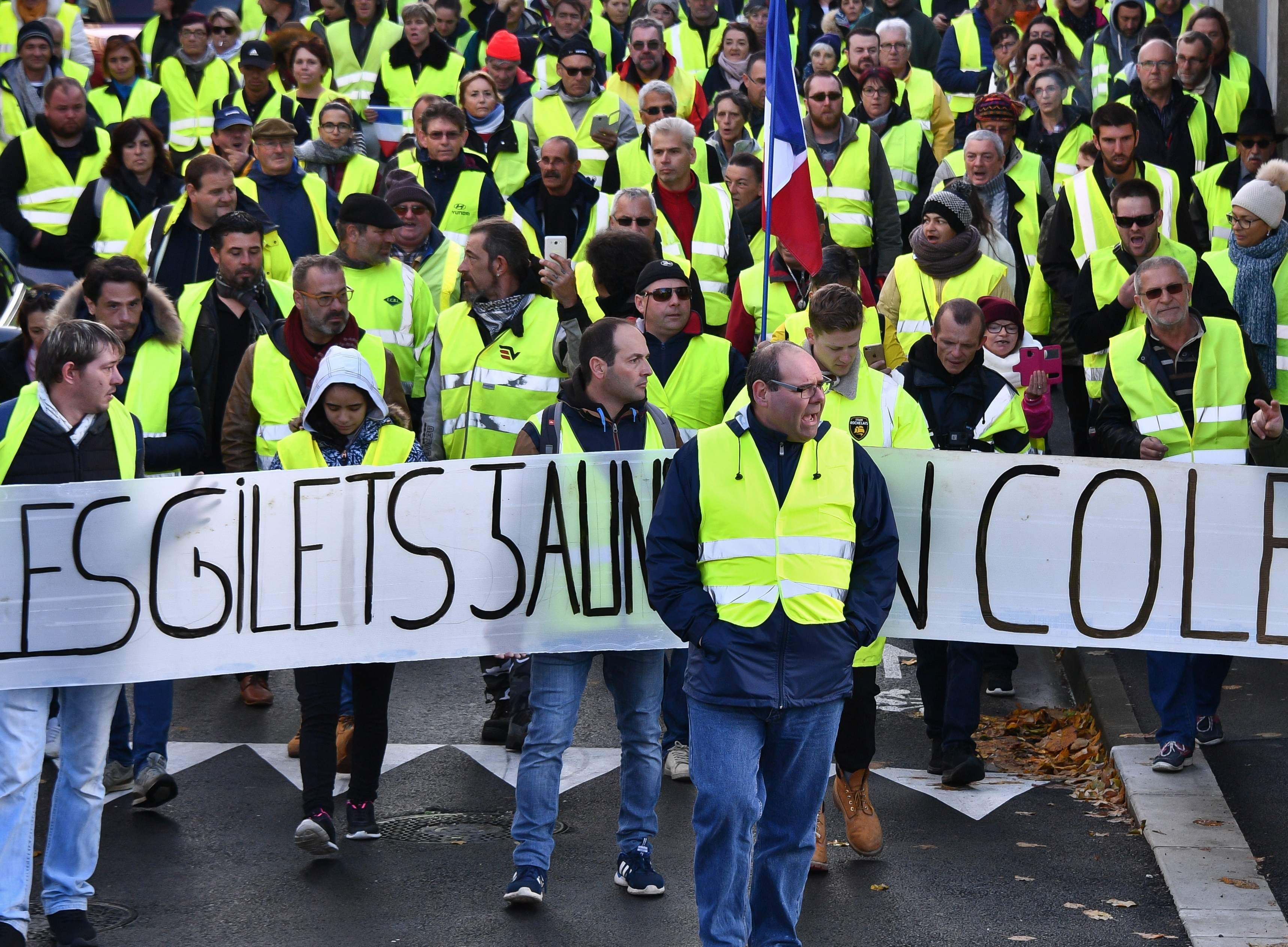 "Yellow Vests march behind a banner reading "" Yellow vests are angry"" as they participate in a protest rally against high fuel prices in Rochefort, south-western France on Nov. 24, 2018, part of a movement which has mushroomed into a widespread protest against stagnant spending power under the French President."